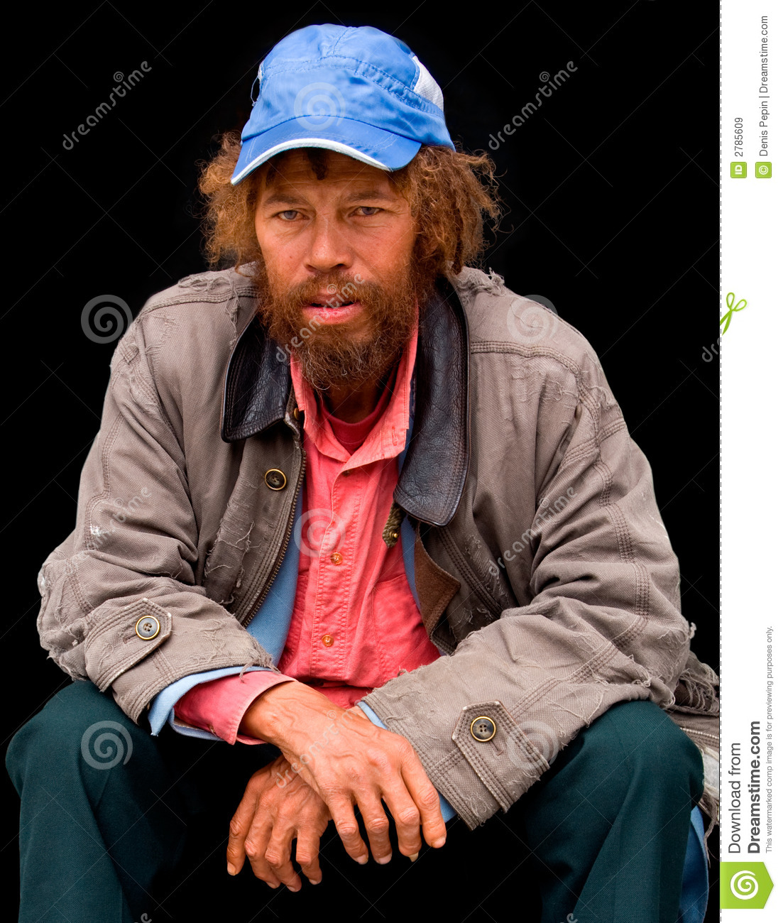 An homeless person is sitting while looking at the camera.