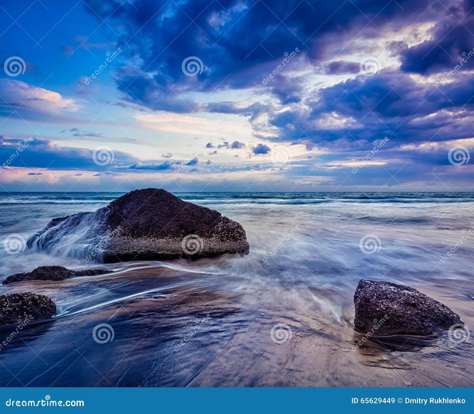 Vagues et roches sur la plage du coucher du soleil