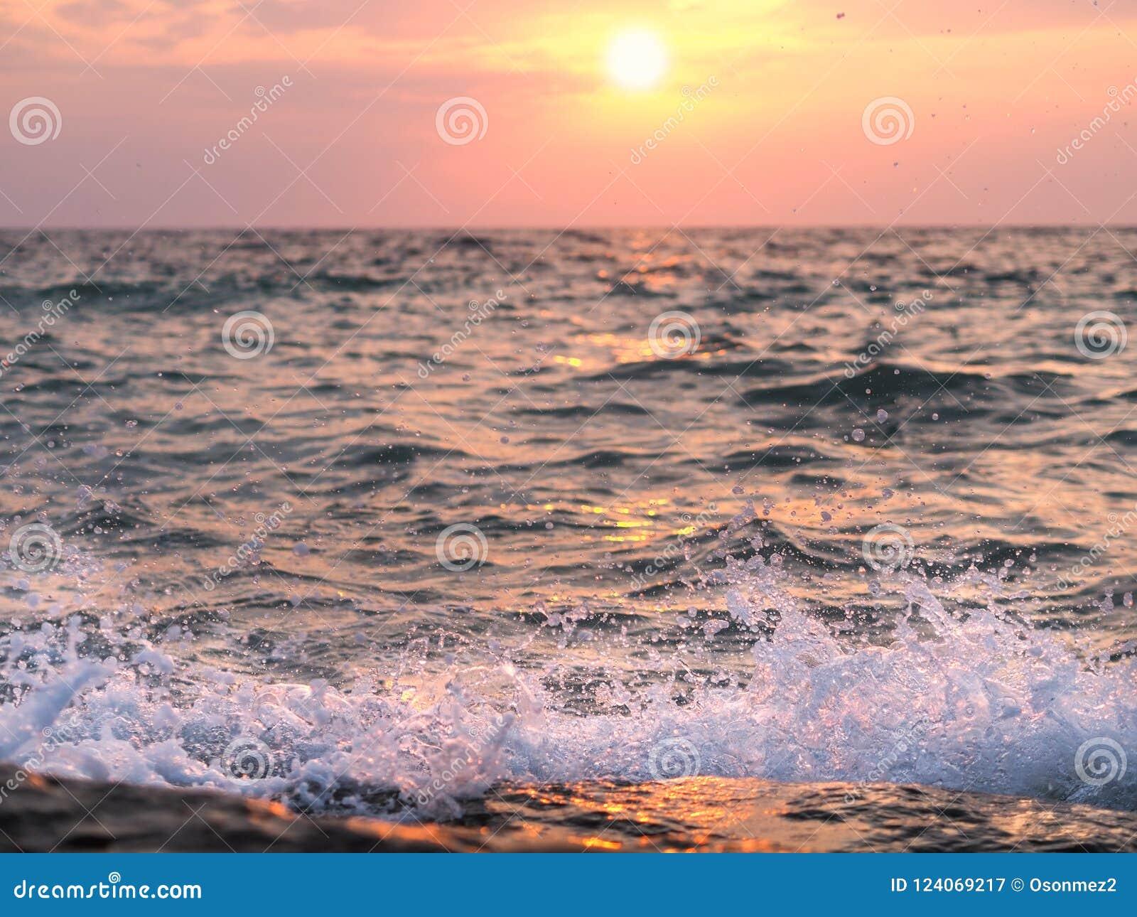 Vagues frappant les rivages rocheux au coucher du soleil