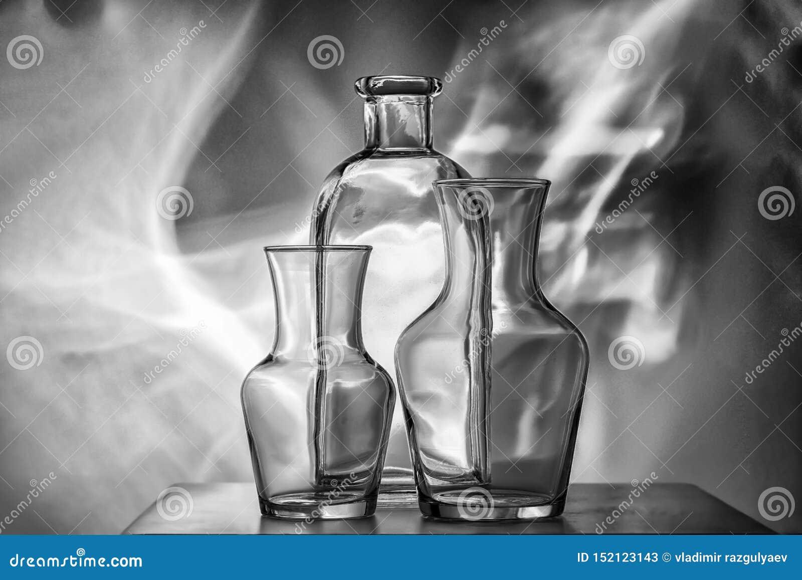 Vajilla-botellas transparentes de cristal de diversos tamaños, tres pedazos en una foto blanco y negro vida inmóvil muy hermosa
