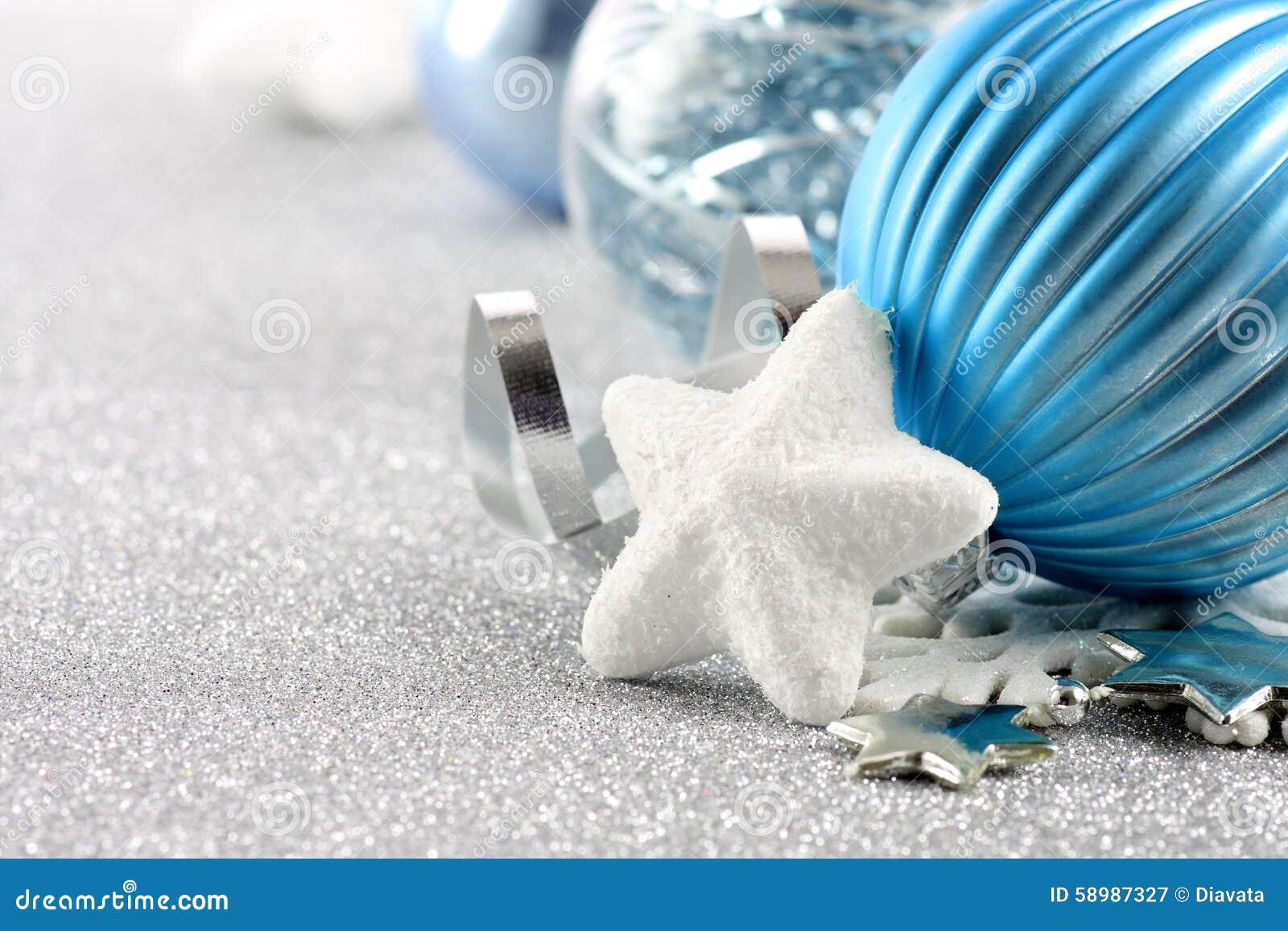 Vakantieachtergrond met witte sneeuwvlok en blauwe Kerstmisornamenten