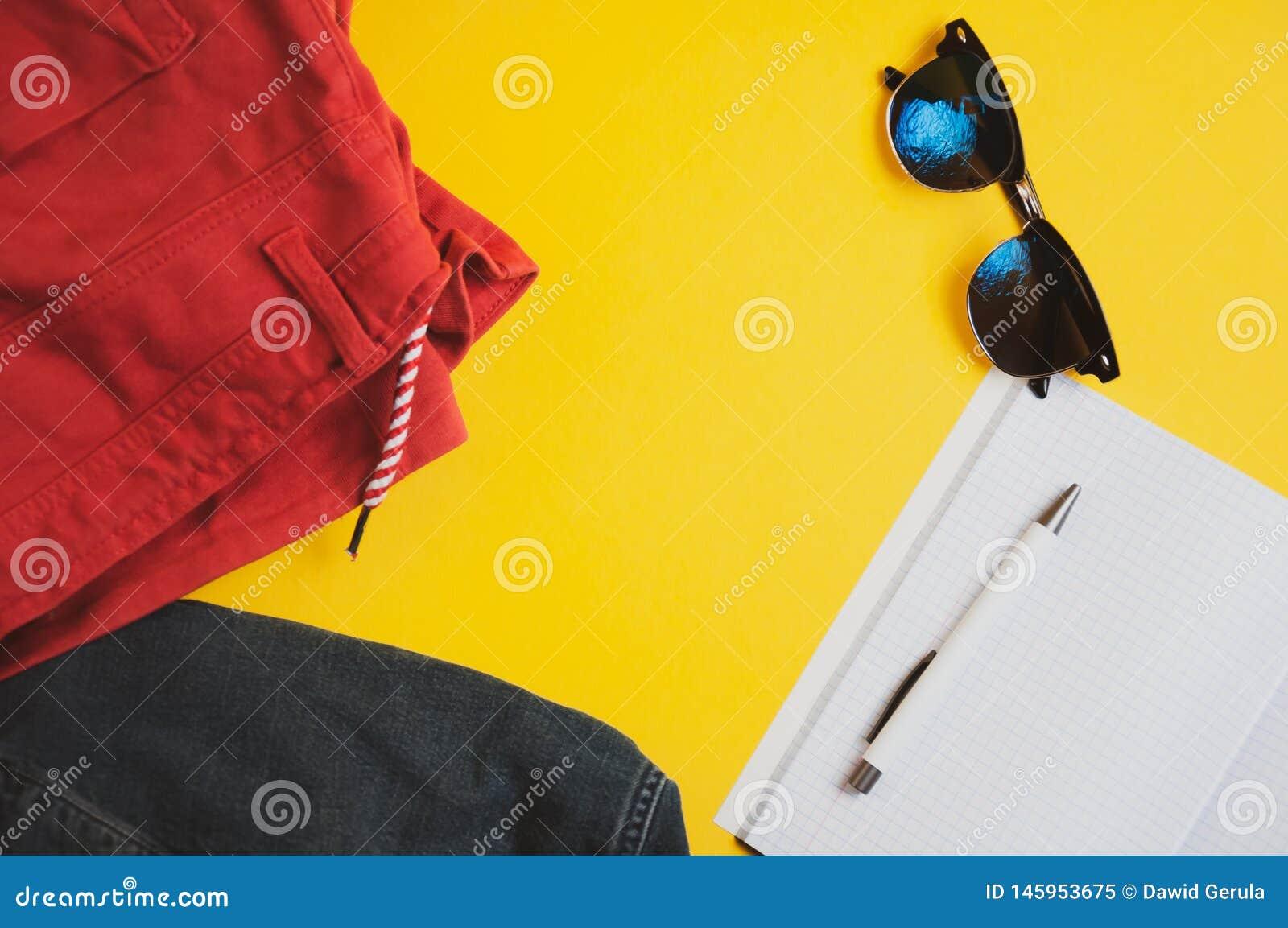 Vakantiemateriaal Hoogste mening van rode borrels, denimjasje, zonnebril en notitieboekje met pen op gele achtergrond