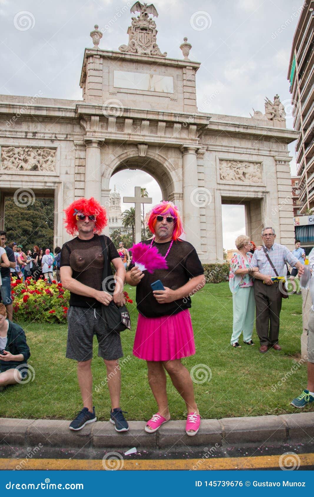 Valência, Espanha - 16 de junho de 2018: Dois pessoas na parada do dia do orgulho alegre na frente de um monumento com uma cruz g