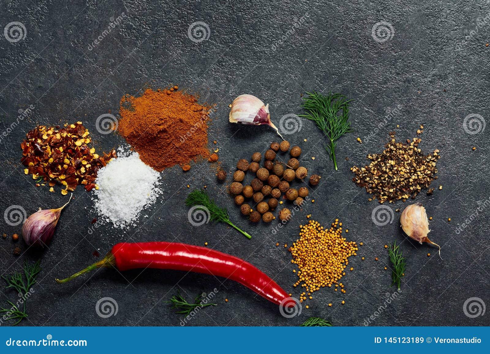 Val av krydda?rter och gr?splaner Ingredienser f?r matlagning Matbakgrund p? svart kritiserar tabellen