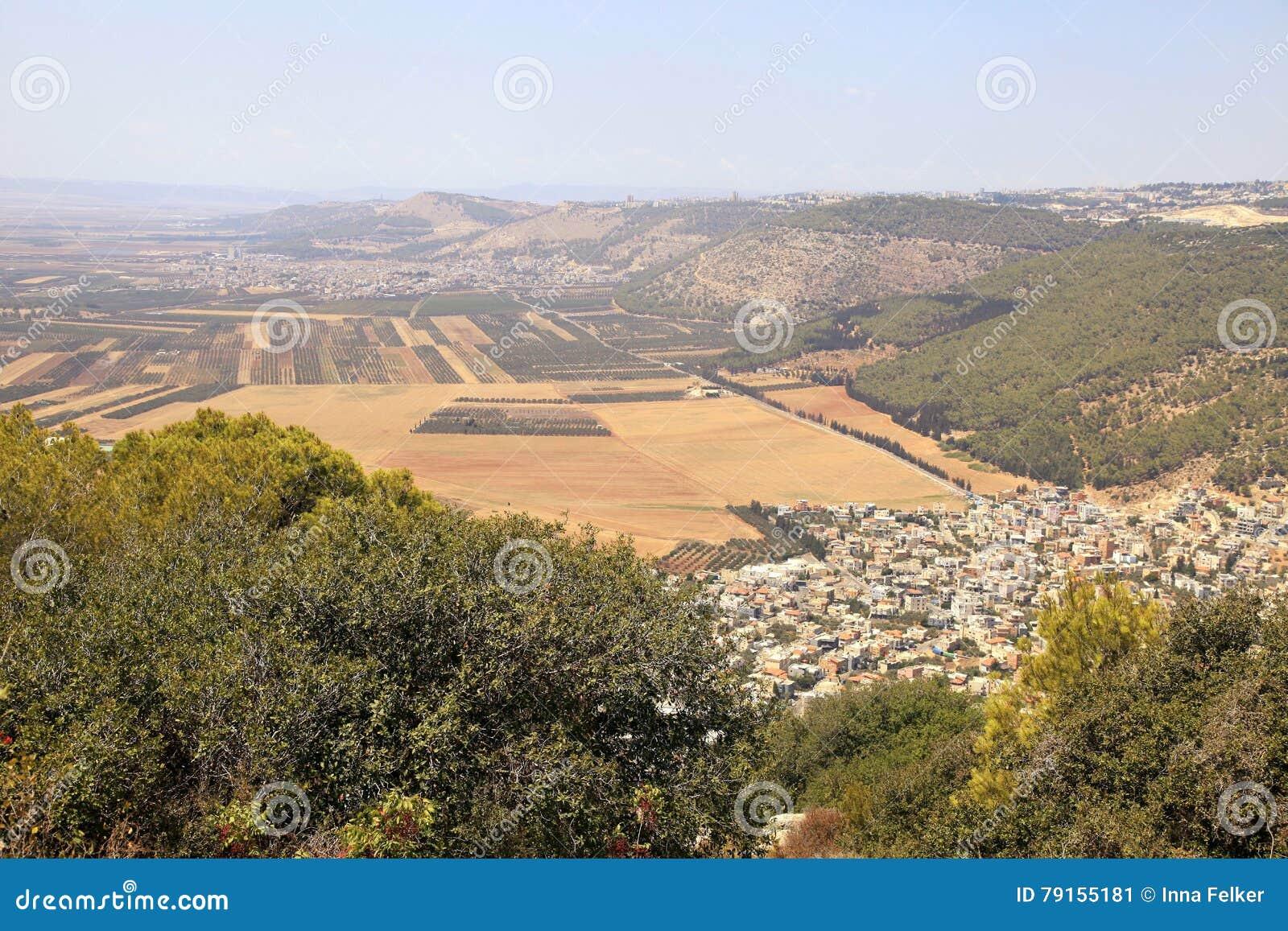 Vale da agricultura com campos e a vila árabe, Israel