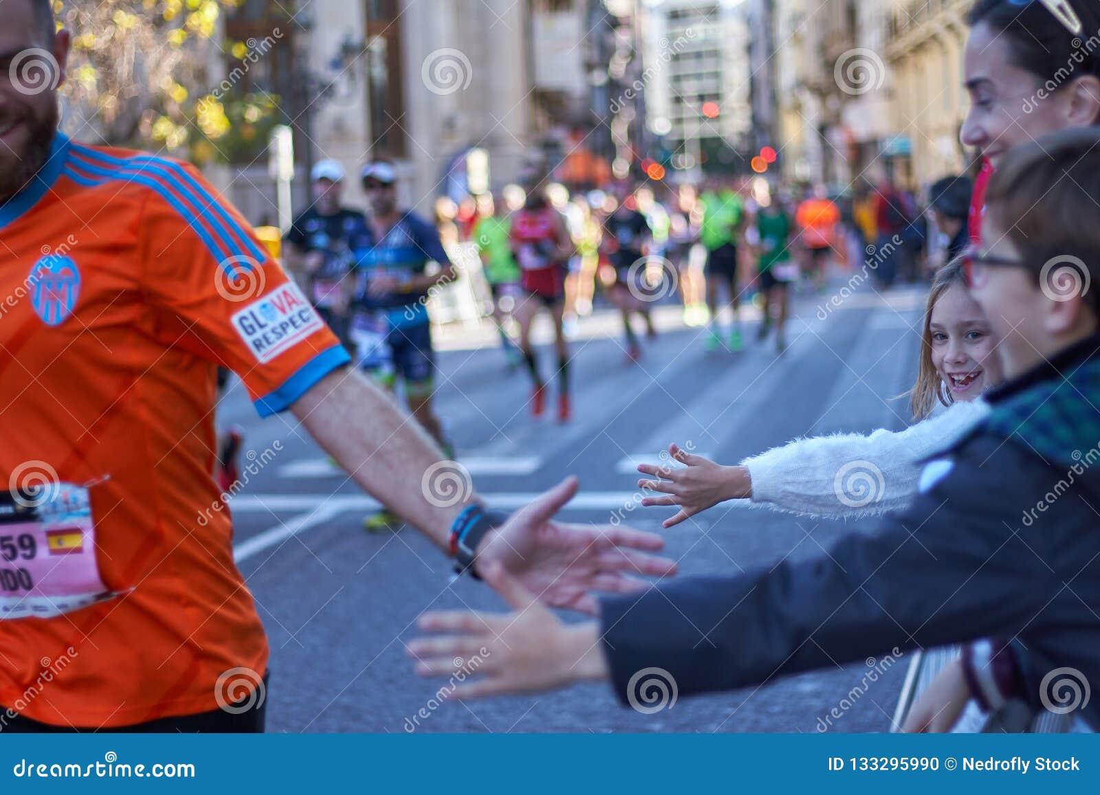VALENCIA, ESPAÑA - 2 DE DICIEMBRE: Los corredores sacuden las manos con los asistentes en el XXXVIII Valencia Marathon el 18 de d