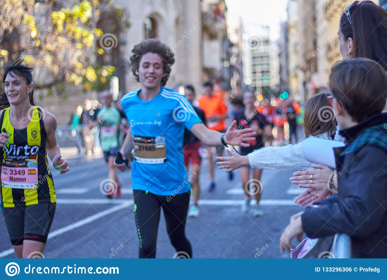 VALENCIA, SPAIN - DECEMBER 2: Runners shake hands with attendees at the XXXVIII Valencia Marathon on December 18, 2018 in Valencia