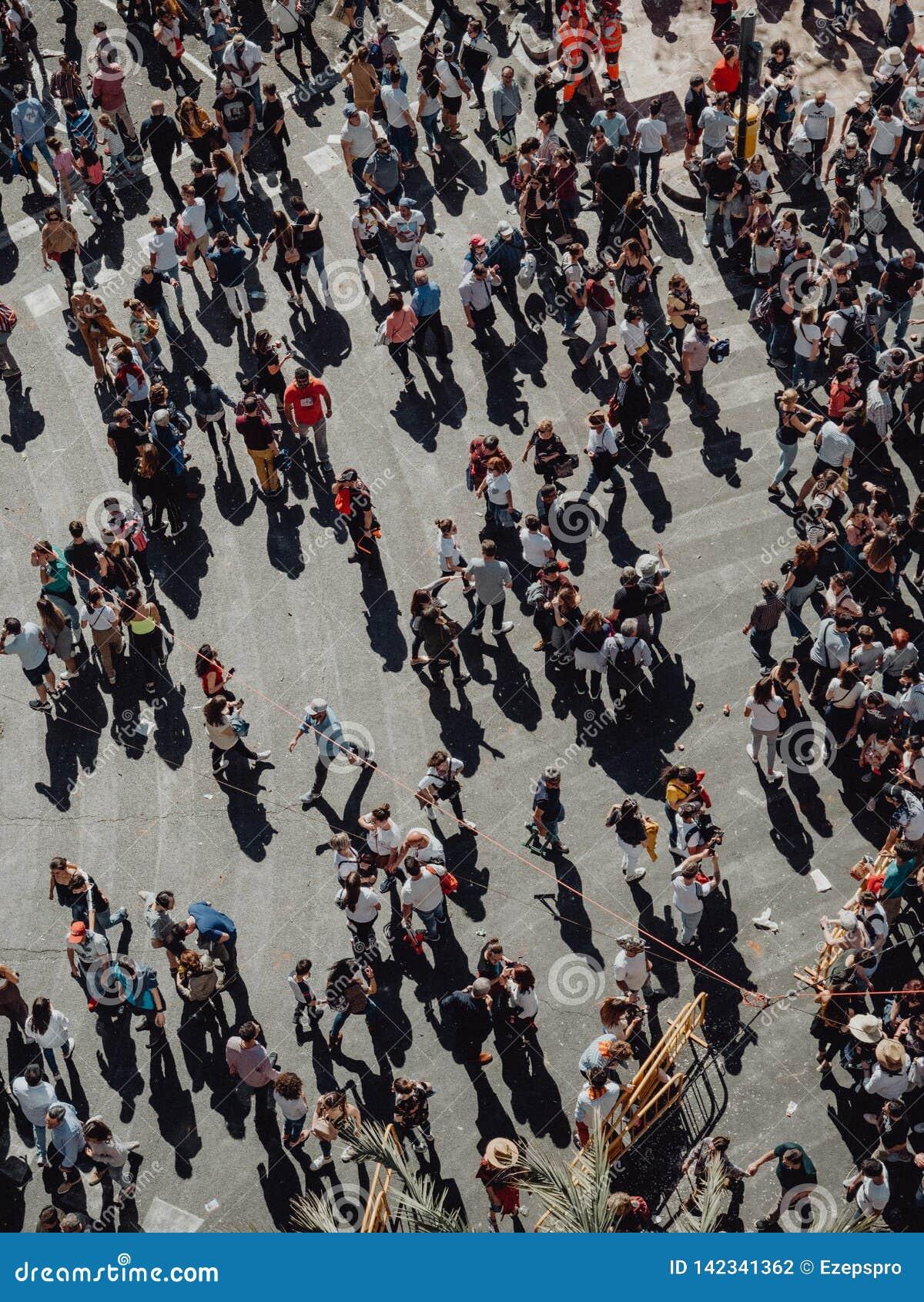 Valencia - Spanien, mars 17, 2019: Folkmassa av folk till och med gatorna av Valencia i den Fallas folkmassan av folk som går gat