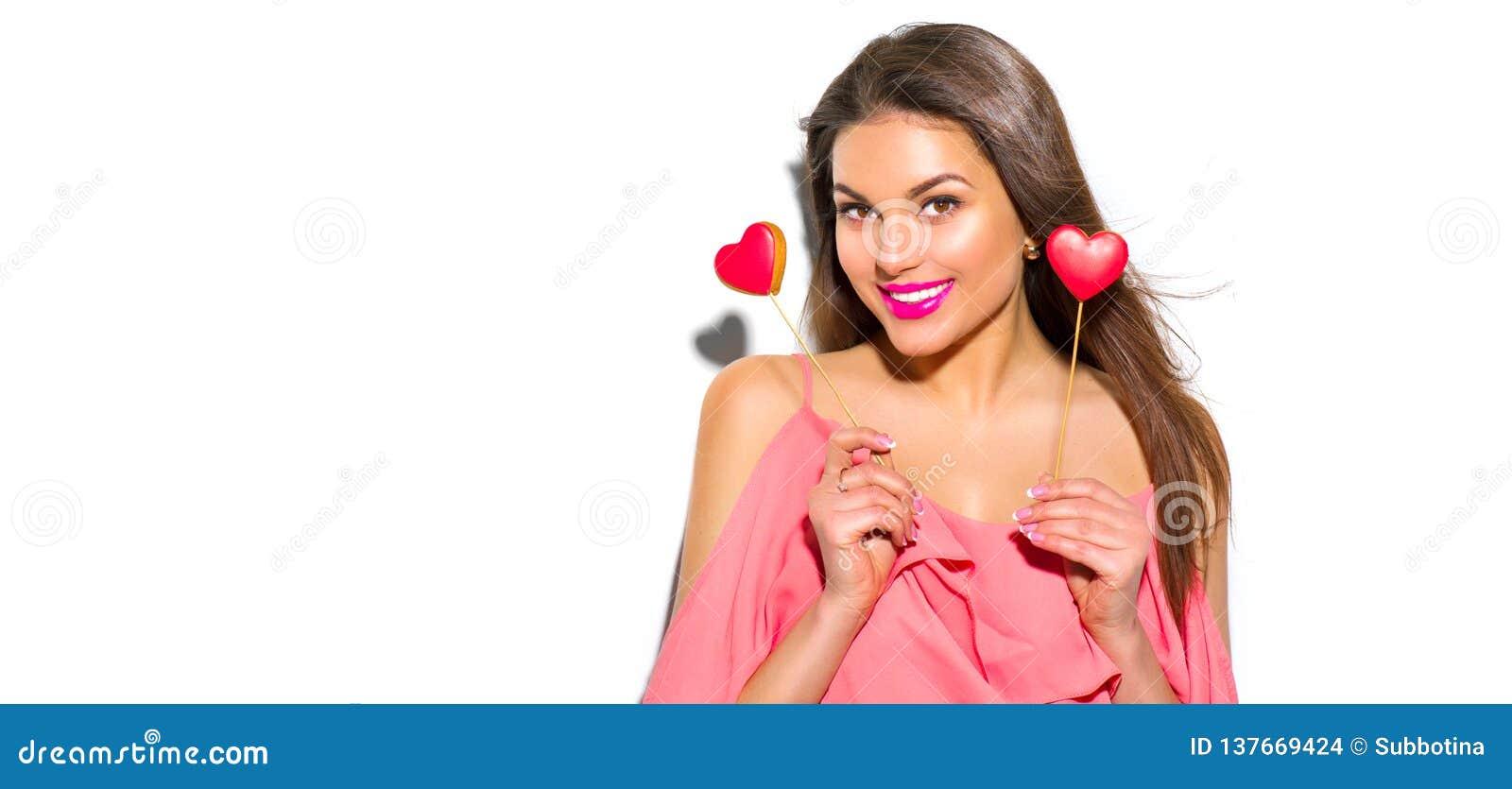 Valentin för dag s För modemodellen för skönhet formade den glade unga flickan med valentinhjärta kakor