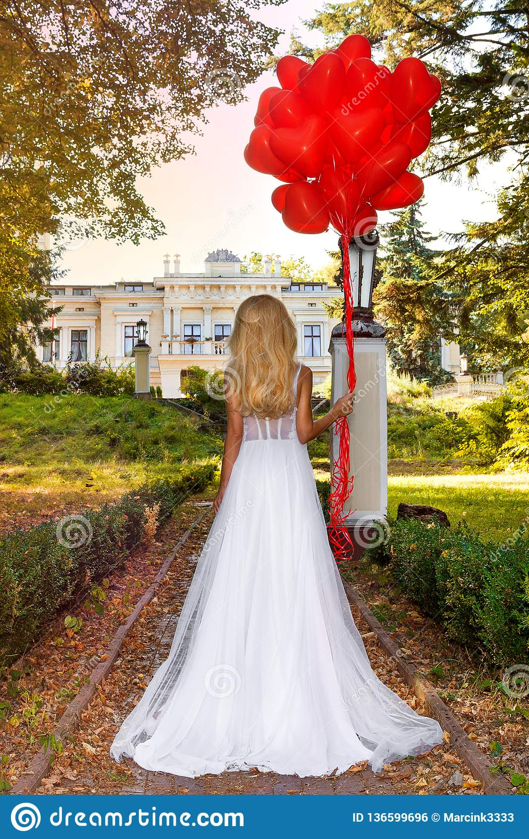 Valentine Beautiful girl with red balloons laugh, in the park. Beautiful happy young woman. Birthday party and bride at the