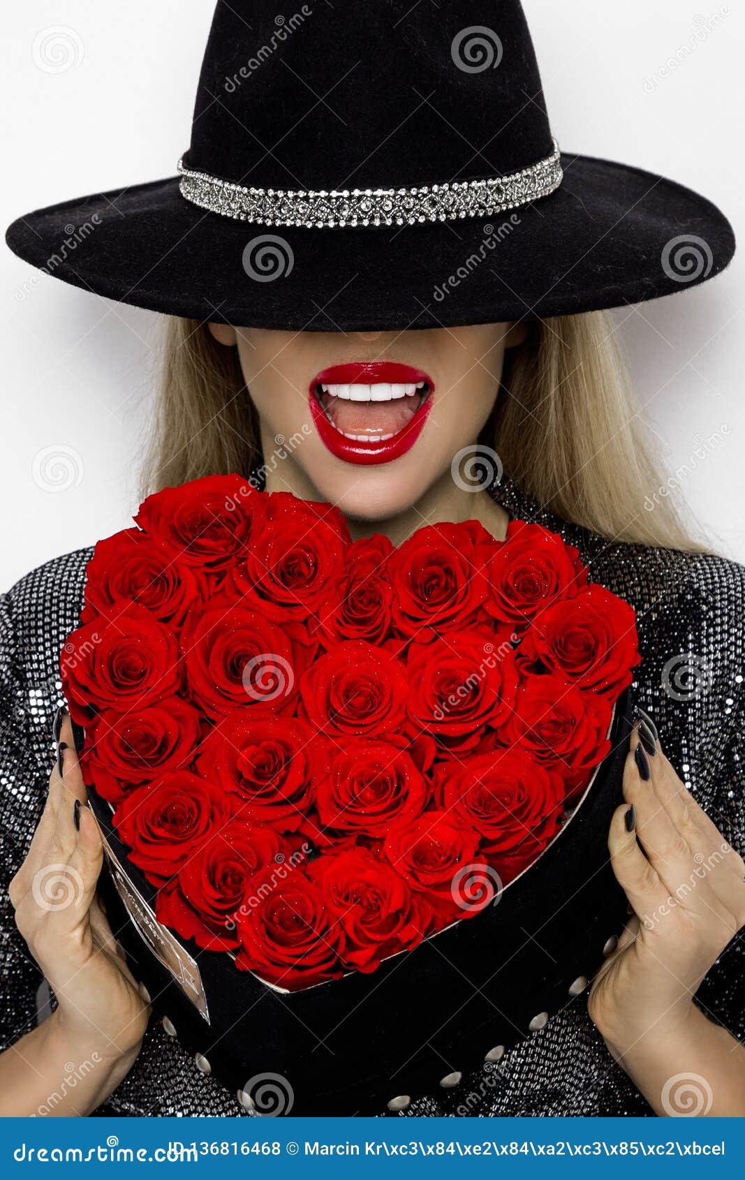Valentine Beauty-Mädchen mit roten Herzrosen Porträt eines jungen weiblichen Modells mit Geschenk und Hut, lokalisiert auf Hinter