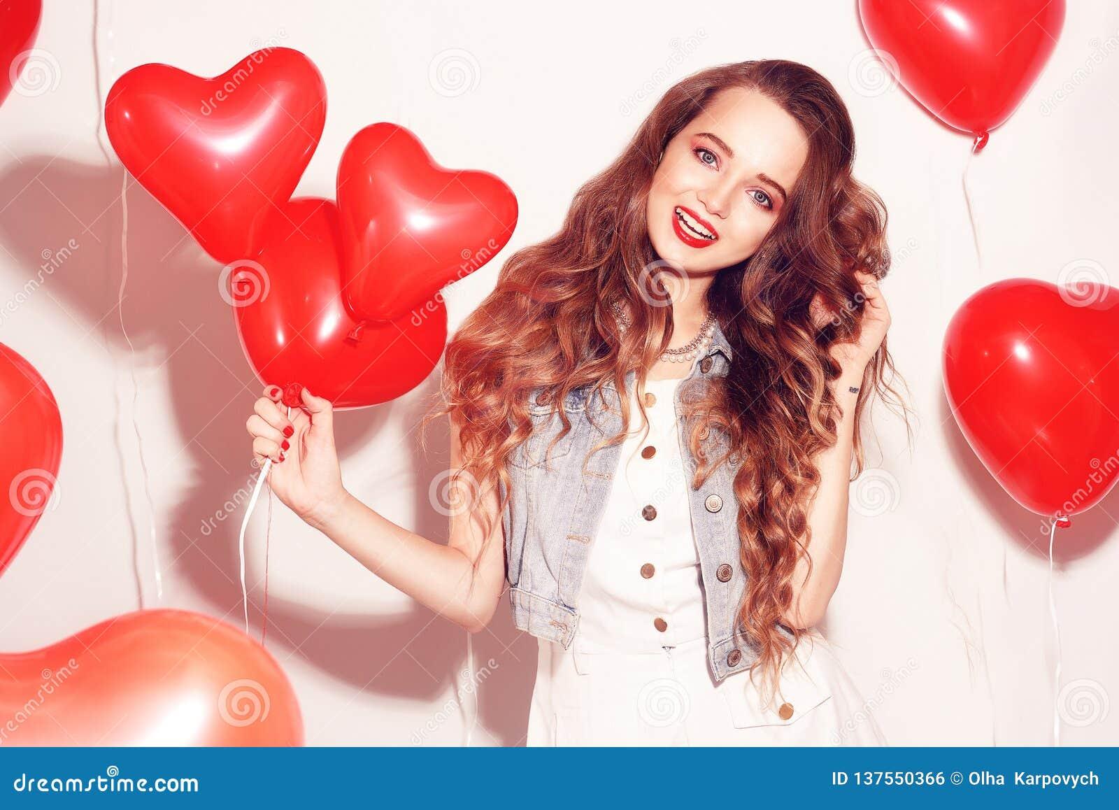 Valentine Beauty-Mädchen mit roten Luftballonen lachend, auf weißem Hintergrund Schöne glückliche junge Frau Der Tag der Frau Url