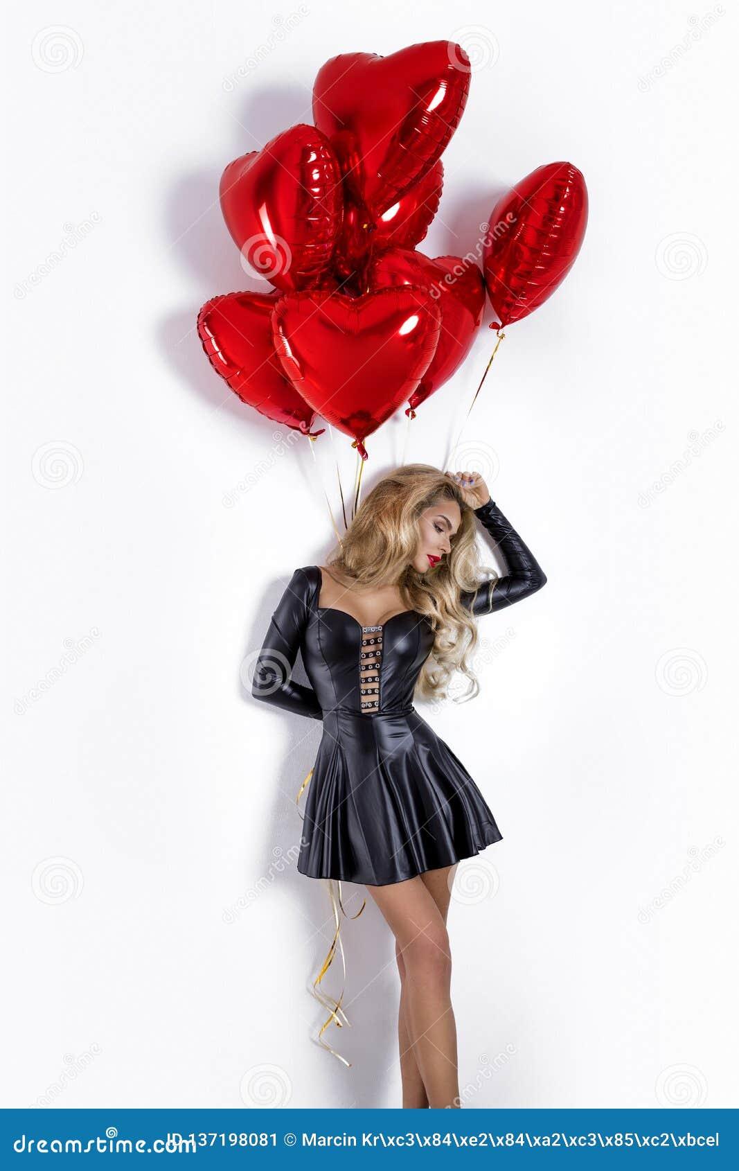 Valentine Beauty-meisje met rode die luchtballon op witte achtergrond wordt geïsoleerd Mooie Gelukkige Jonge vrouw die product vo