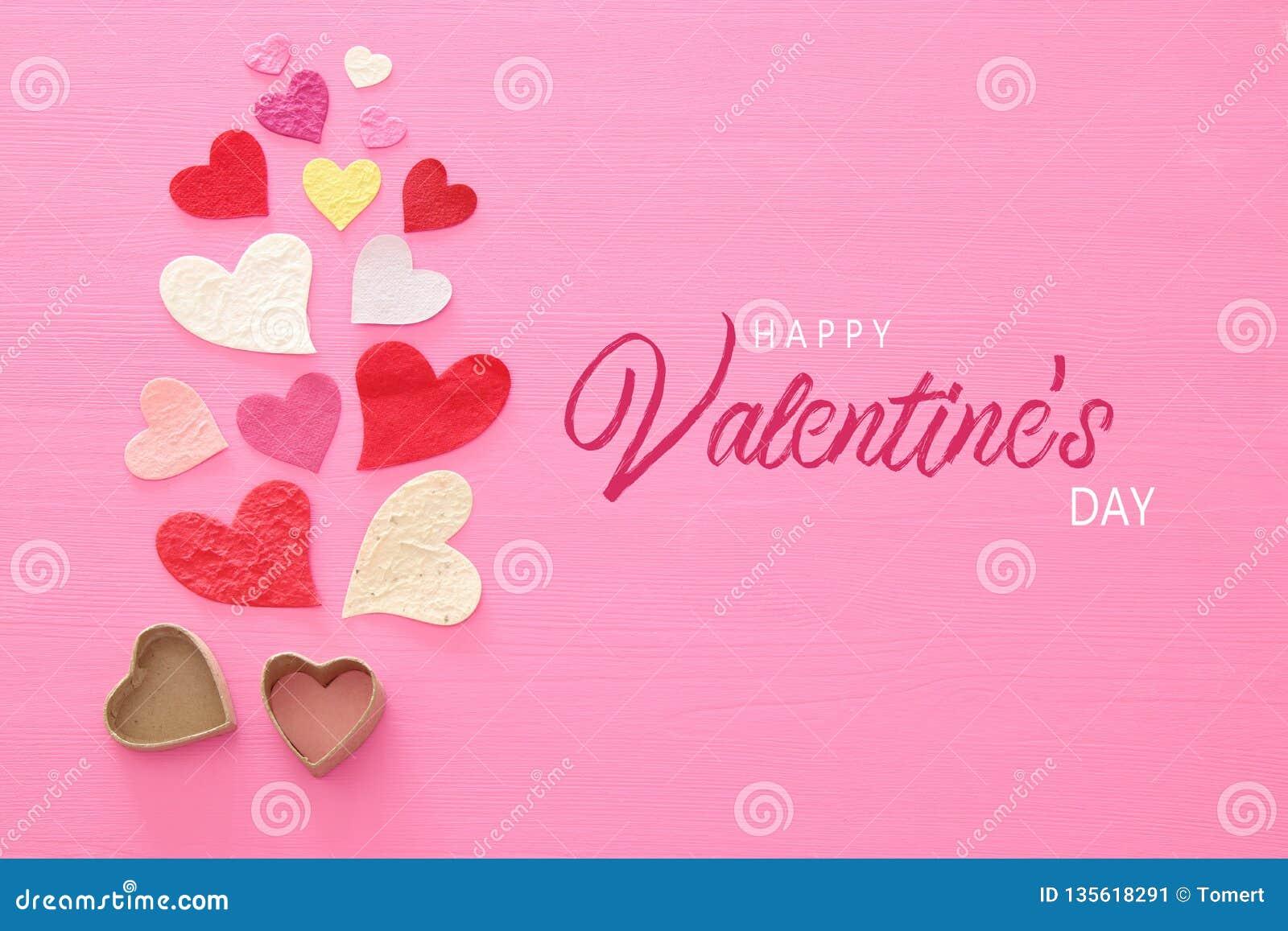 Valentine' conceito do dia de s Corações de papel sobre o fundo cor-de-rosa de madeira Configuração lisa