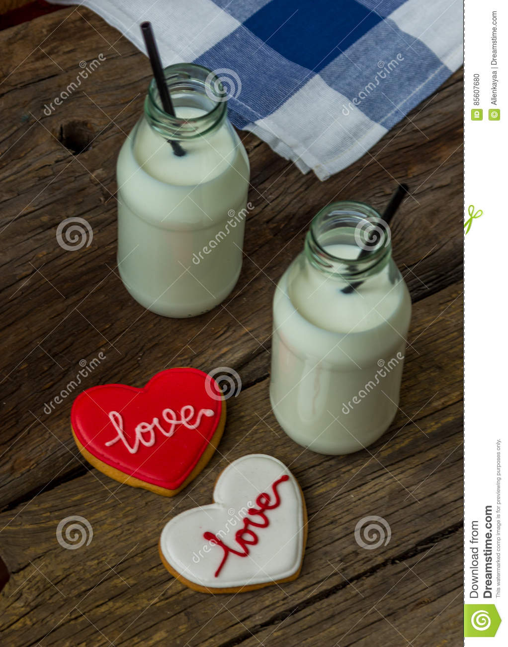 Valentine cookies and milk in a bottle on a wooden background