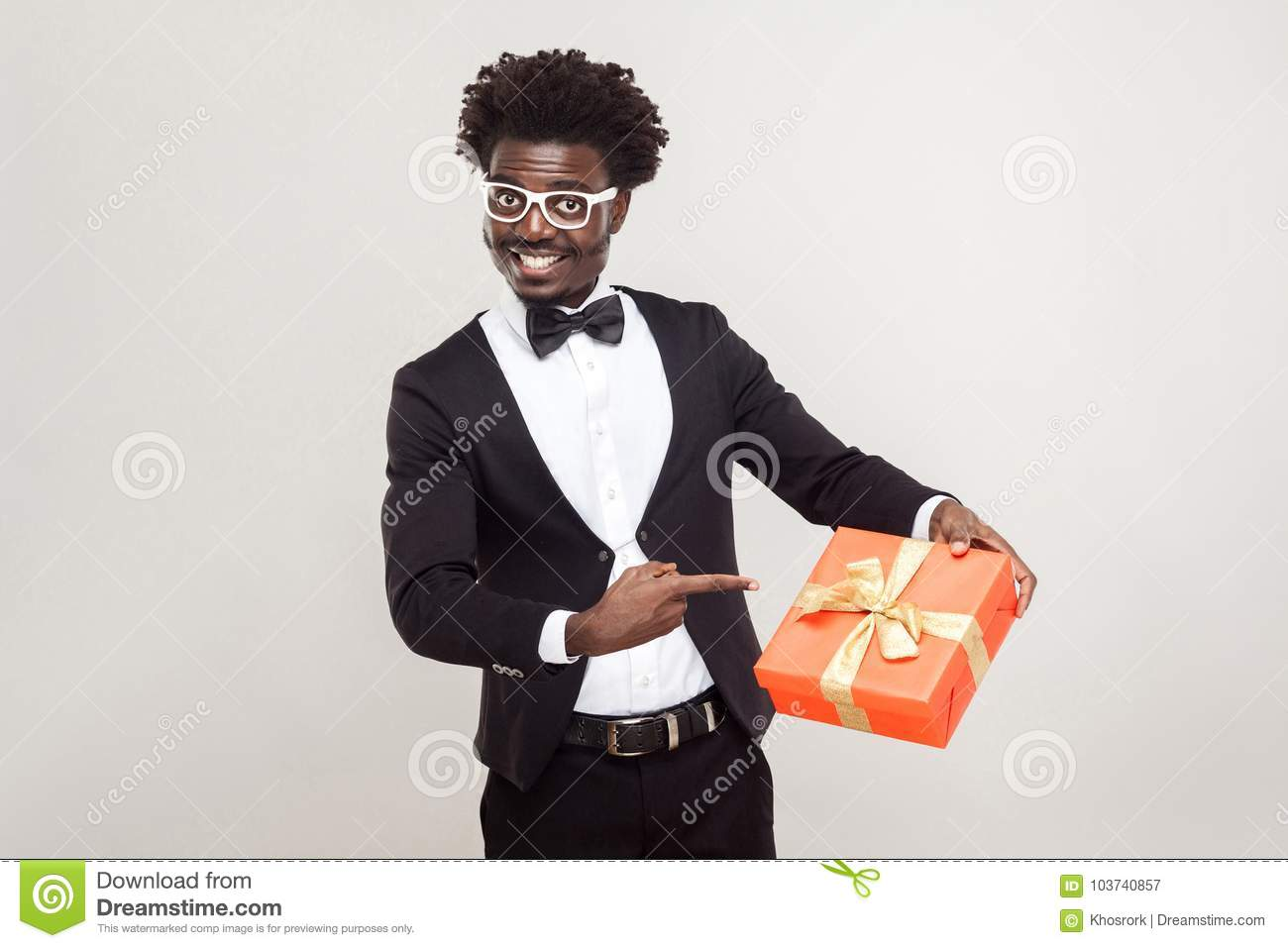 Valentine day. African businessman pointing fingers at gift box