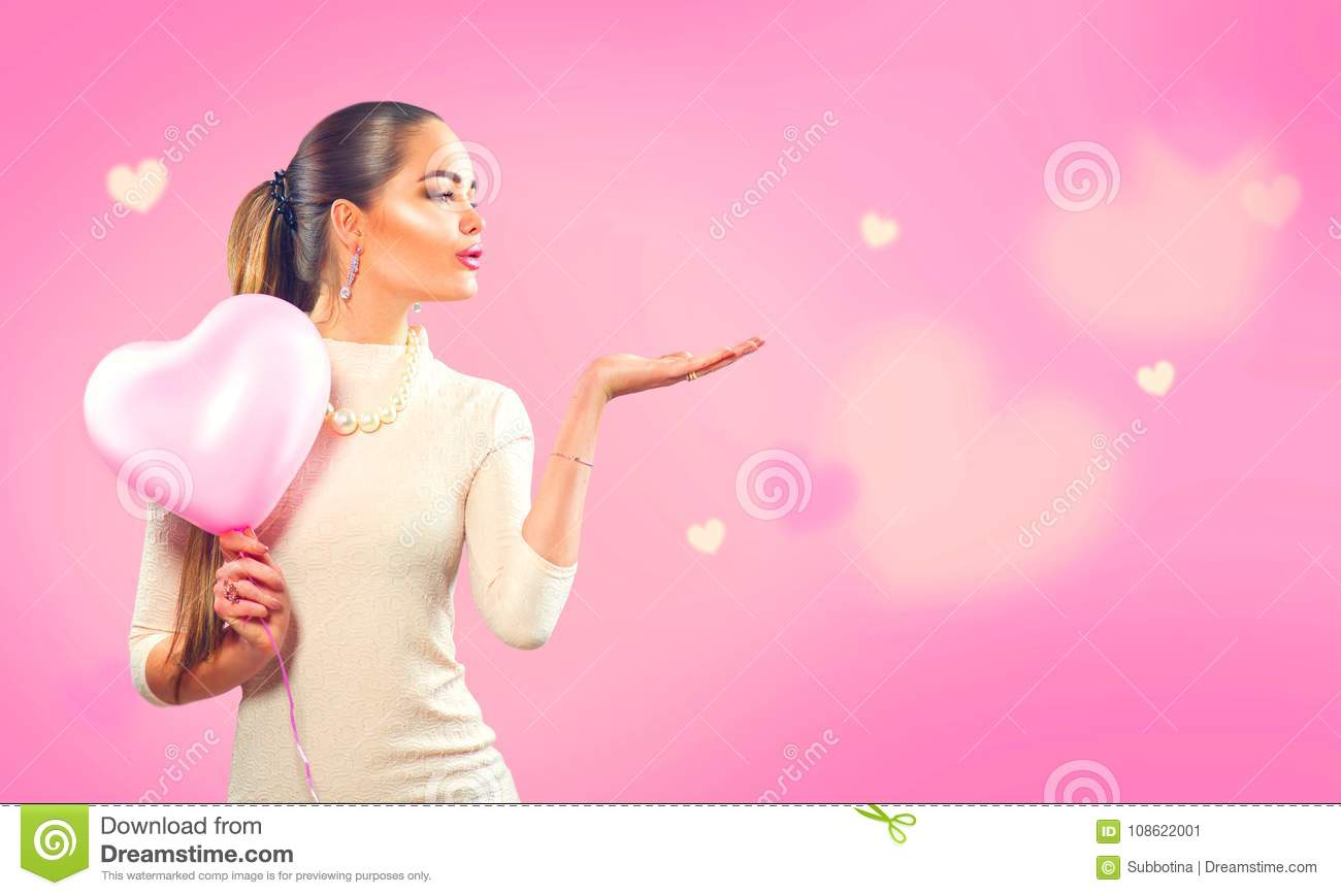 Valentine`s day. Beauty girl with pink heart shaped air balloon pointing hand