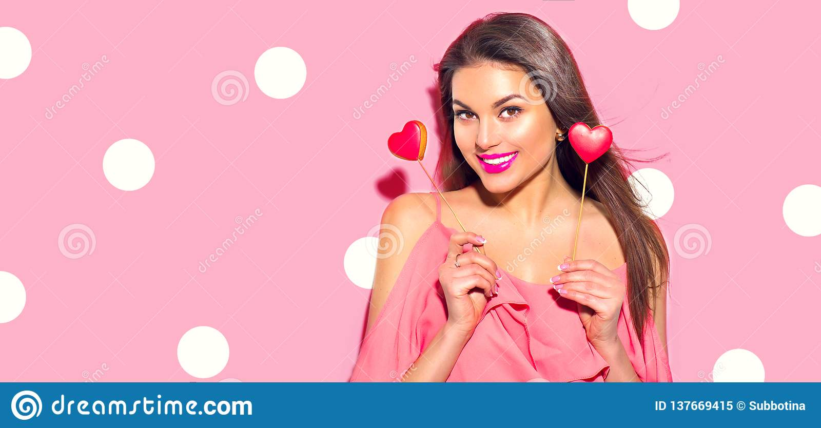Valentine`s Day. Beauty surprised young fashion model girl with Valentine heart shaped cookies