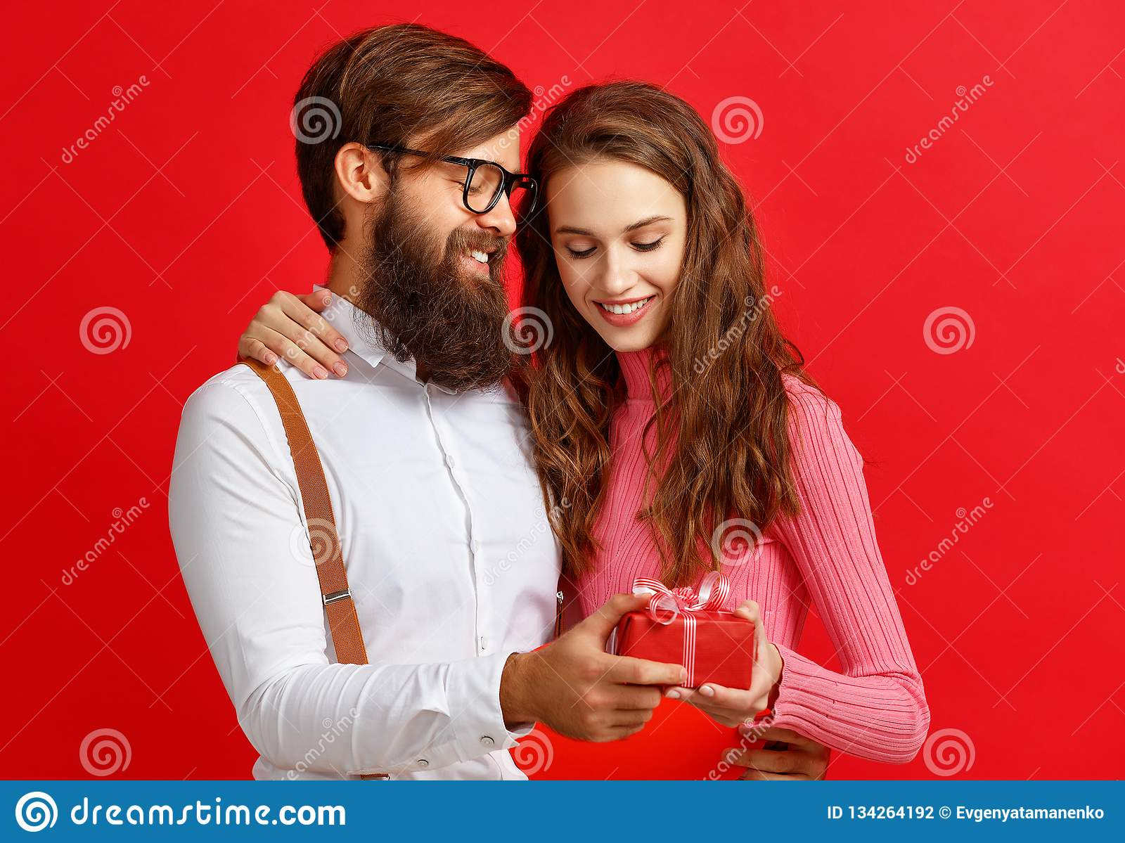 Valentine`s day concept. happy young couple with heart, flowers, gift on red