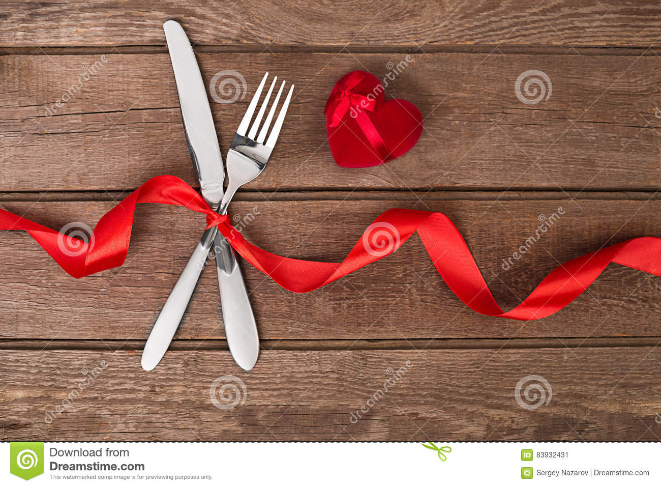 Table Setting Background valentine`s day dinner table setting with red ribbon, knife and
