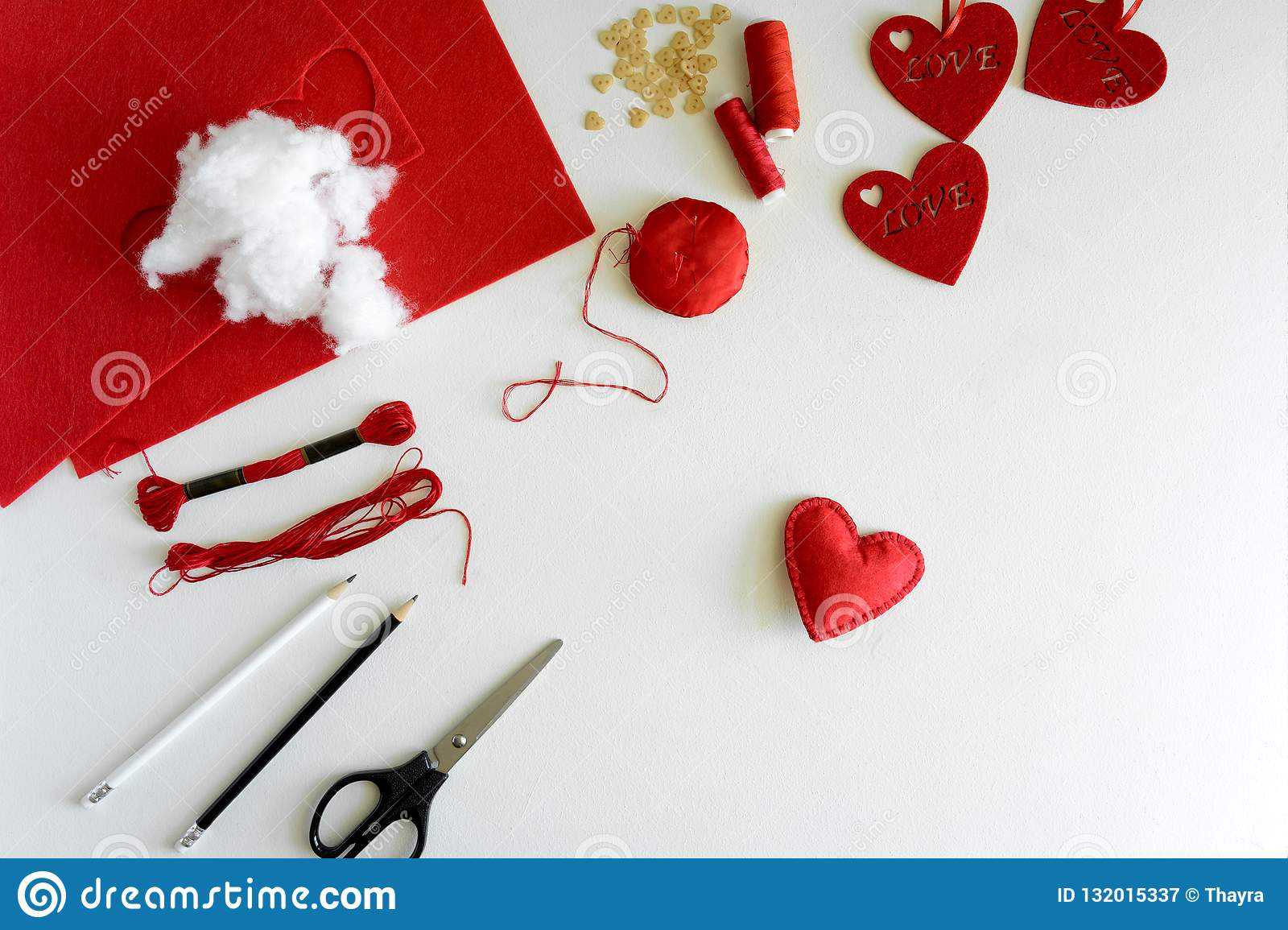 Valentine`s day felt crafts. Woman hands sewing red hearts. DIY. Flat lay. Top view