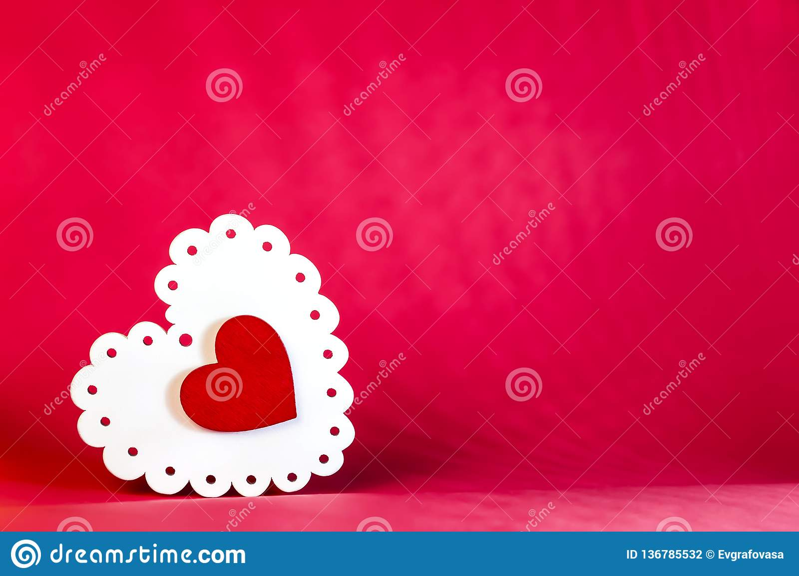 Valentine`s day holiday, mother`s day, March 8, wedding invitation. Symbol of love white wooden heart on a red background with