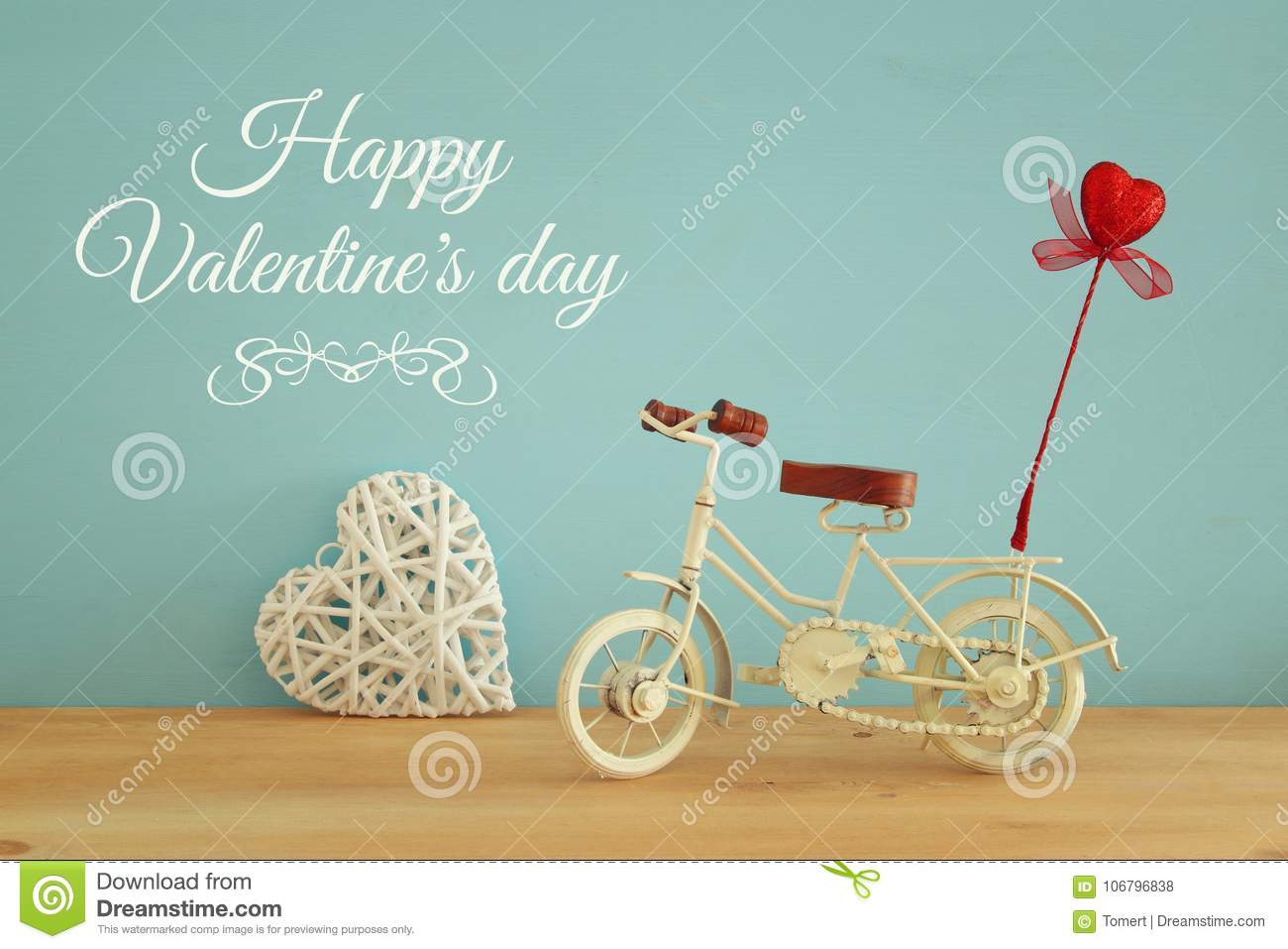 Valentine& x27;s day romantic background with white vintage bicycle toy and glitter red heart on it over wooden table.