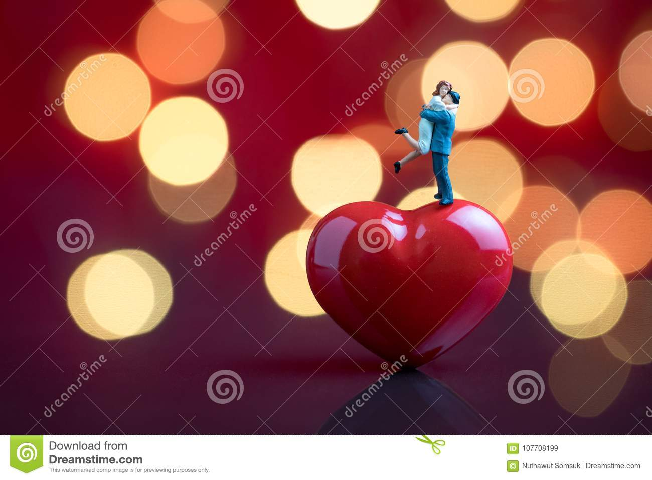 Valentines card or wallpaper with sweet miniature couple standing on red heart shape with red background and beautiful bokeh