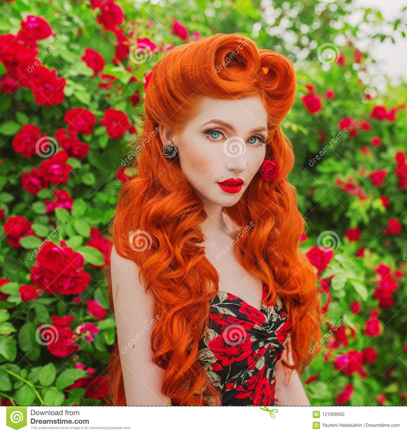 Valentines Day background. Brilliant retro girl with red lips in stylish dress with print of roses in beautiful summer garden. Red