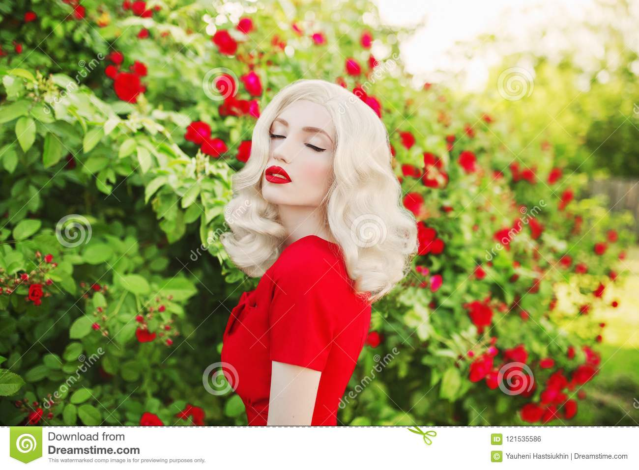 Valentines Day background. Young stunning girl with red lips in stylish dress in beautiful summer roses garden.