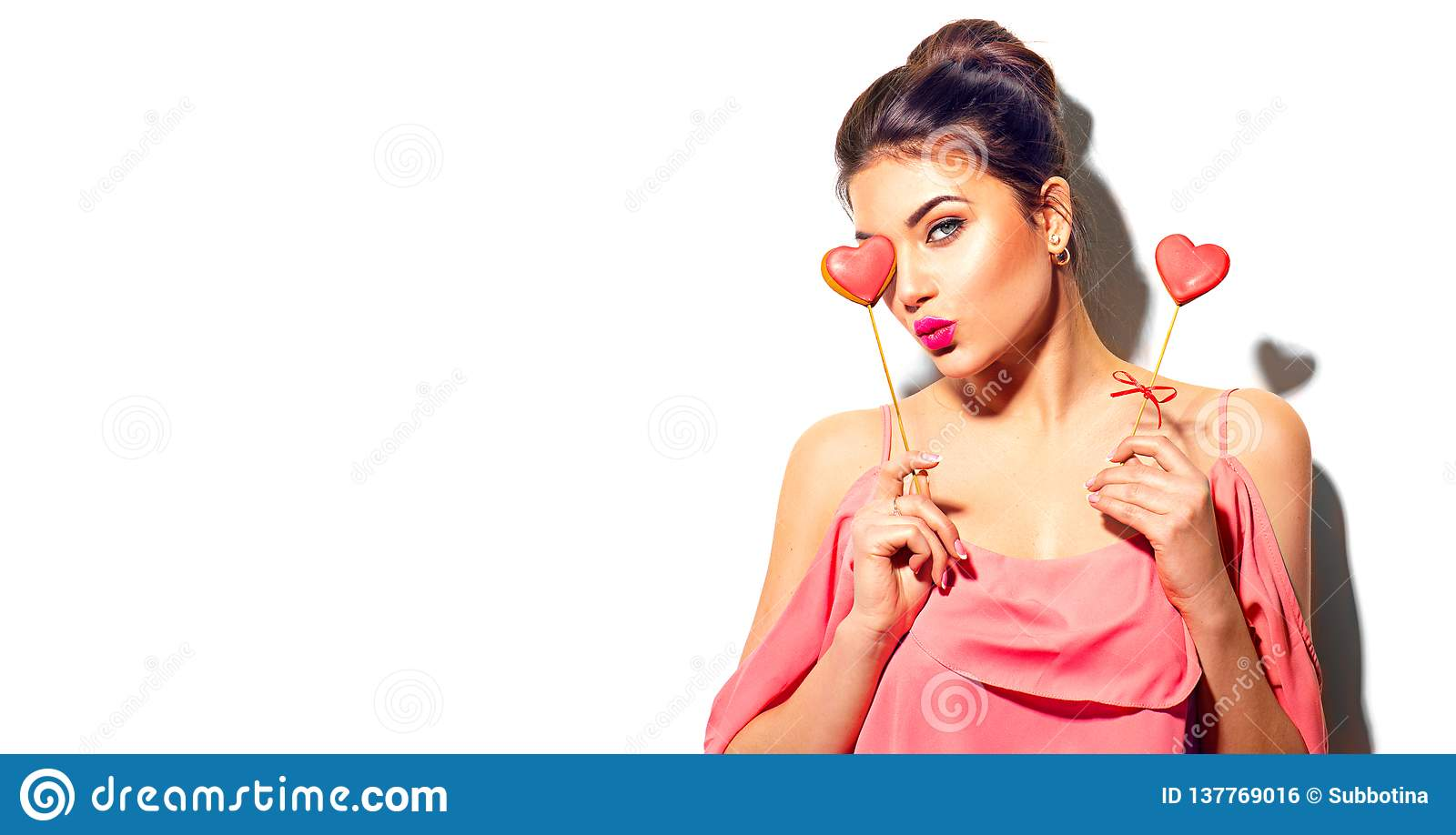 Valentines Day. Beauty joyful young fashion model girl with Valentine heart shaped cookies in her hands