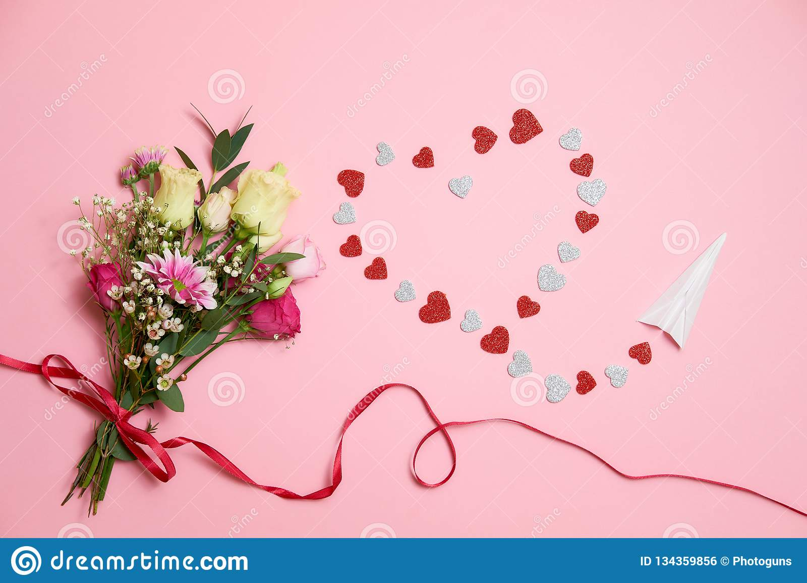 Valentines day composition : bouquet of flowers with ribbon bow, heart heart shape made of valentines cards and paper airplane. lo