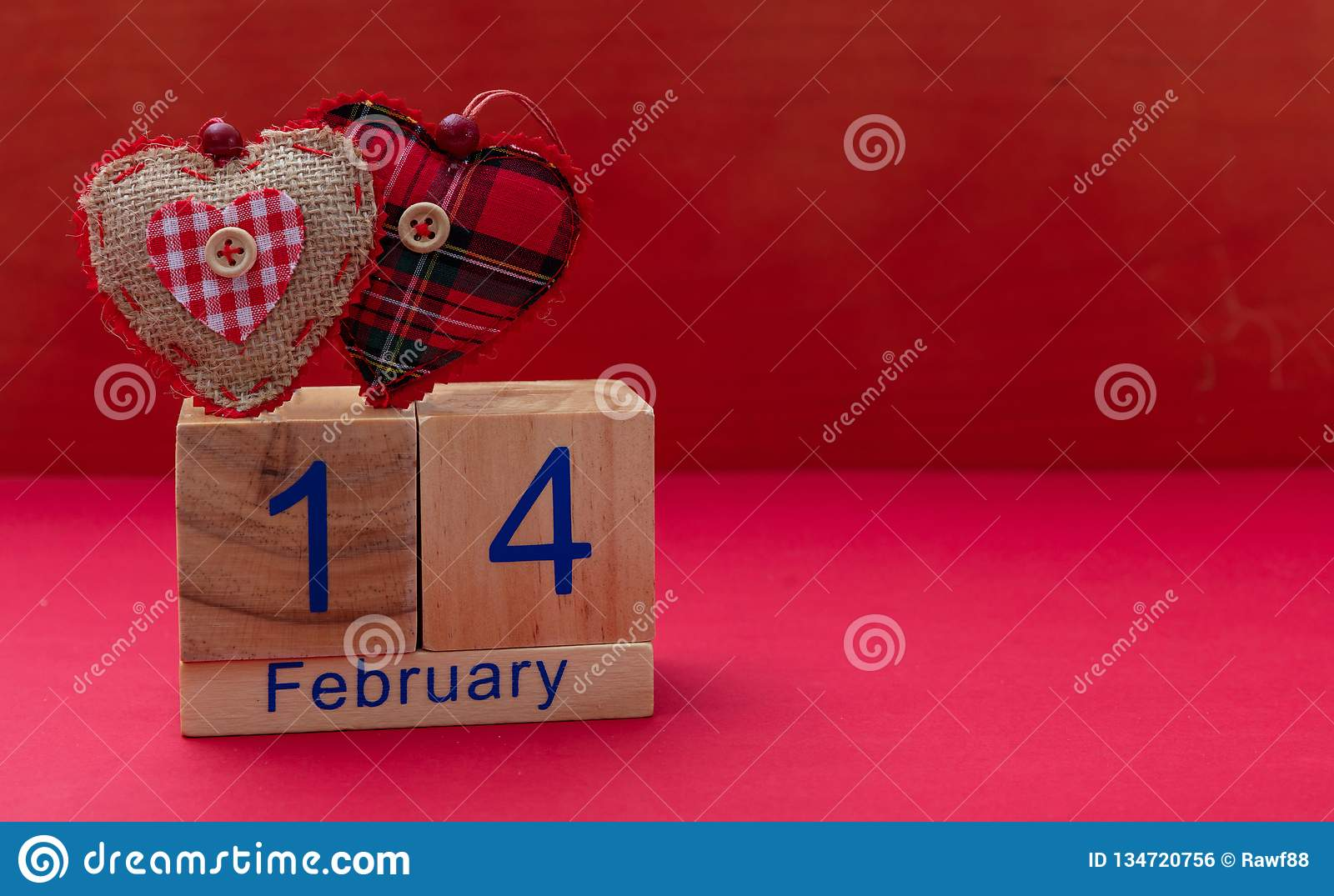 Valentines day. 14 February and two red fabric hearts on red background
