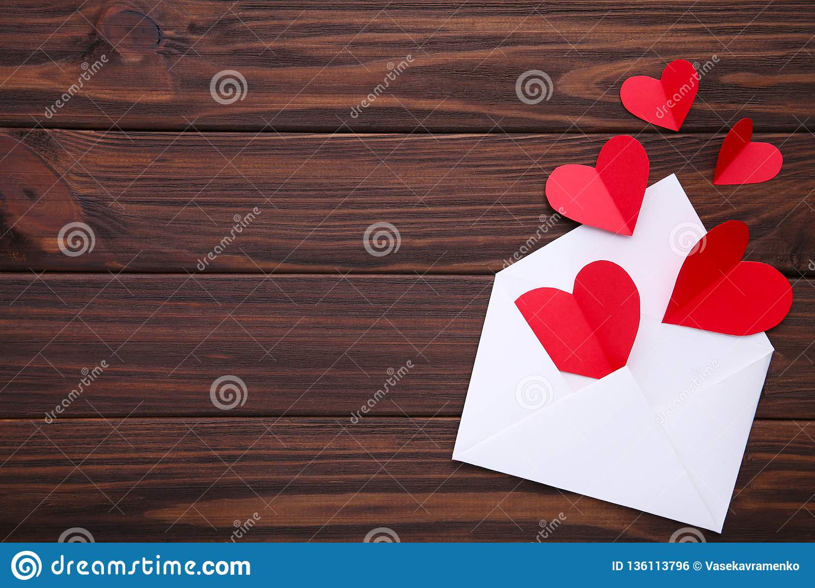 Valentines day greeting card. Handmaded red hearts in envelope on white background