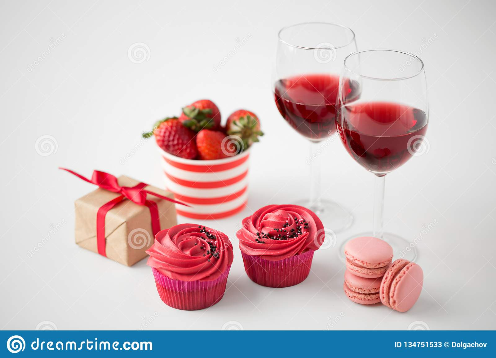 31fd92299ee4 Valentines day and sweets concept - close up of frosted cupcakes, macarons,  strawberries, glasses of red wine and gift box on white background