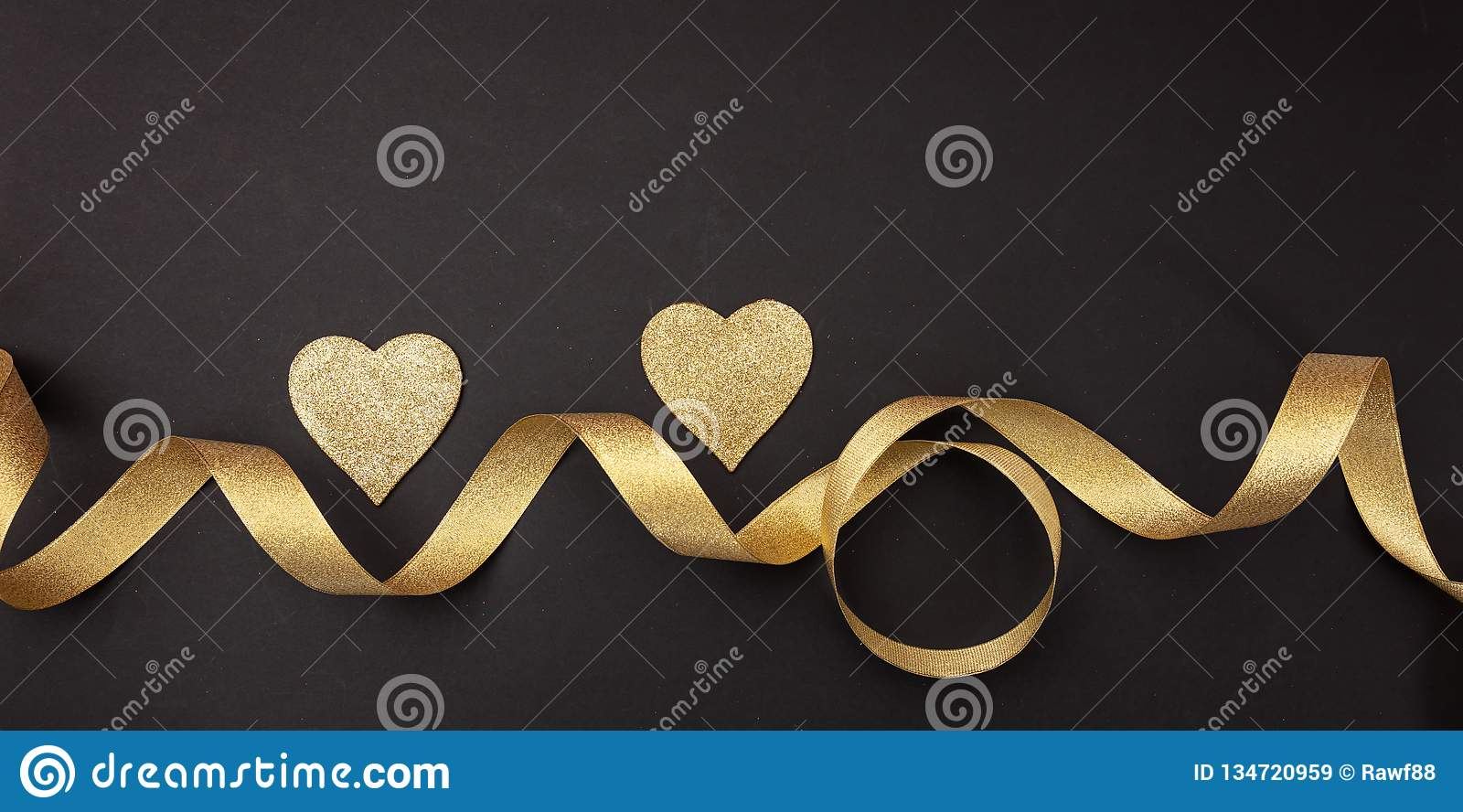 Valentines day. Top view of two golden hearts with satin ribbon against black background