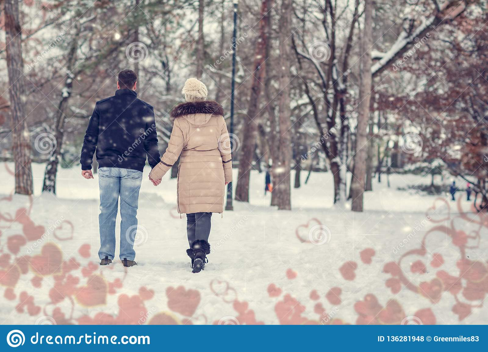 Valentines holiday - young couple having a walk in winter park
