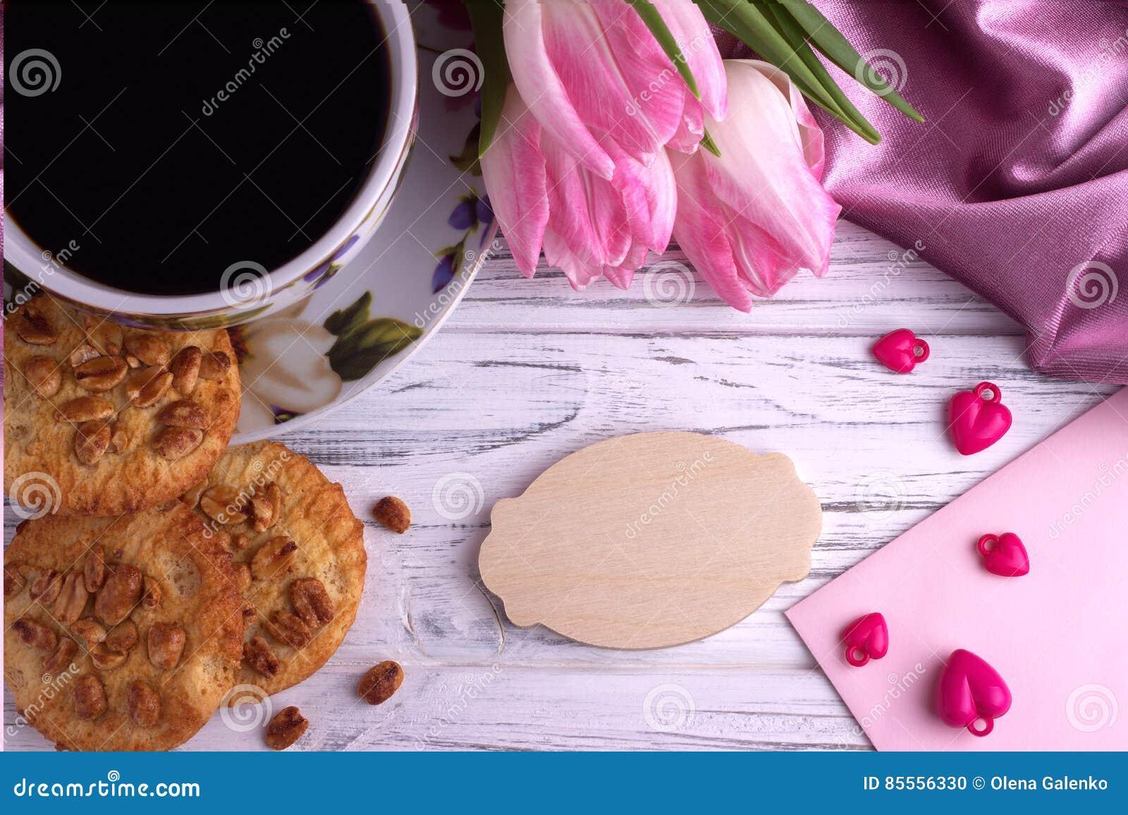 Valentinsgruß ` s Tageselegantes Stillleben mit Tulpe blüht Schale Herz-Formzeichens coffe Eibisches des roten auf weißem hölzern