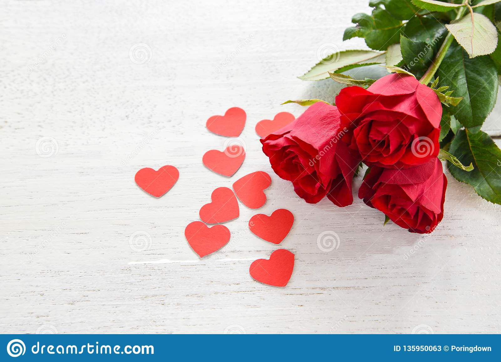 Valentinsgrußtagesrote rosafarbene Blume auf weißem hölzernem Hintergrund/kleinem rotem Herzen der romantischen Liebe