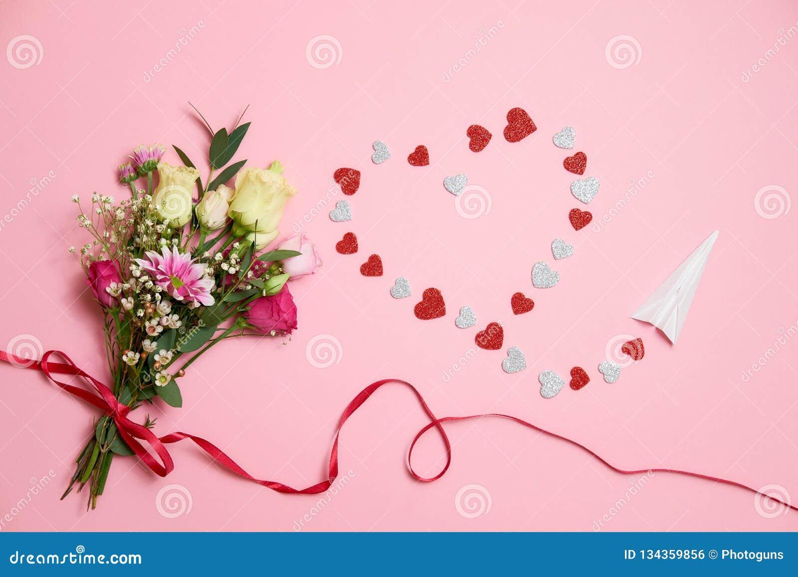 Valentinsgrußtageszusammensetzung: Blumenstrauß von Blumen mit Bandbogen, Herzherzform machte von den Valentinsgrußkarten und vom