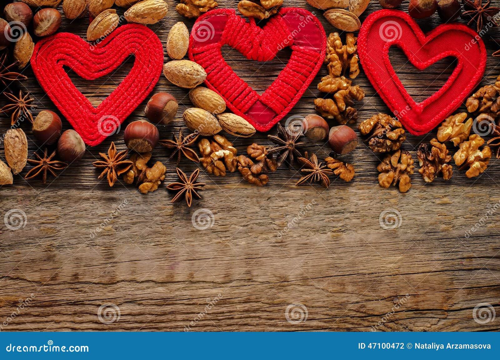 Valentinstaghintergrund mit Herzen und Nüssen