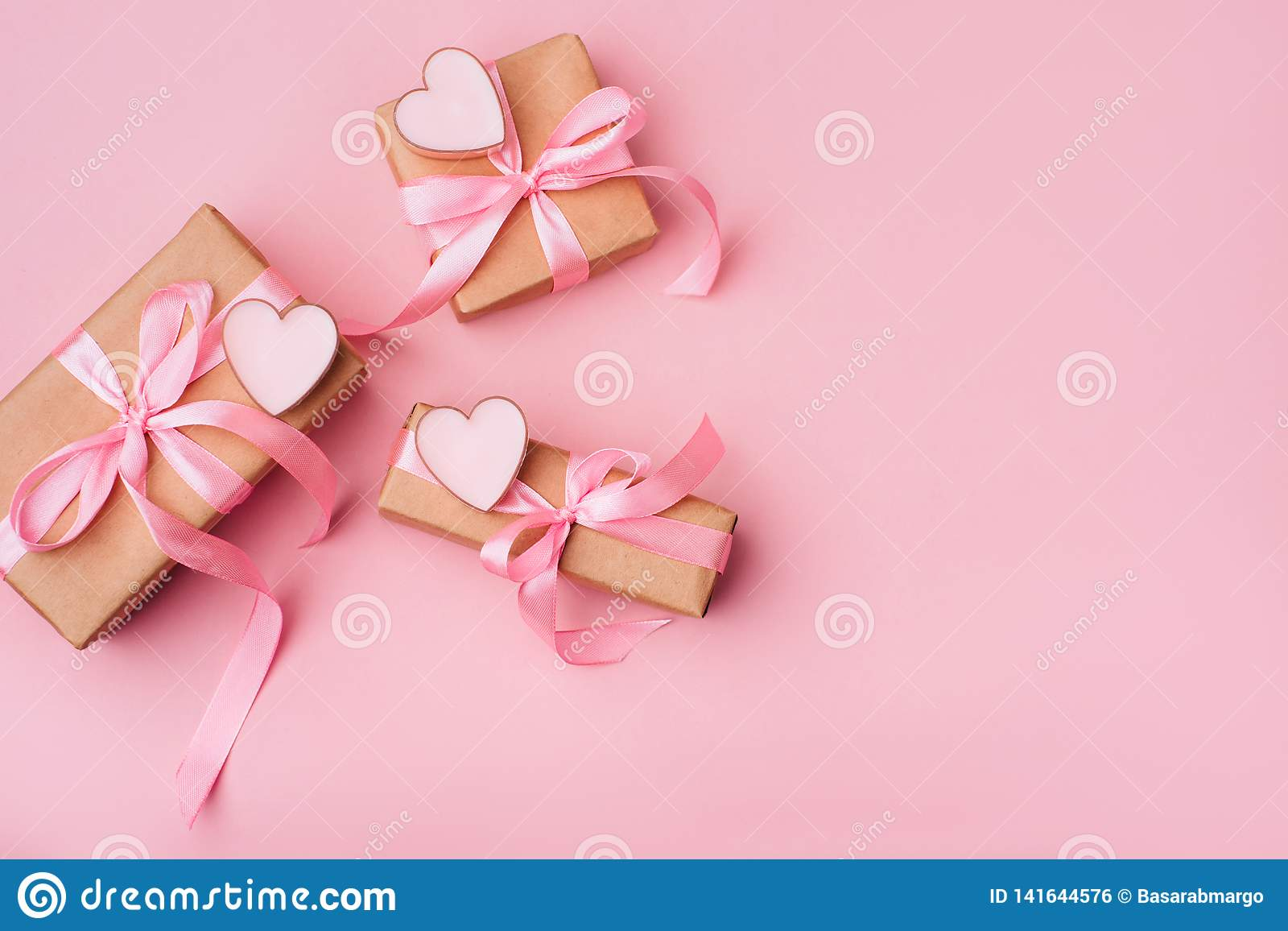 Valentinstagzusammensetzung: weiße Geschenkboxen mit Bogen und rosa Herzen Zu
