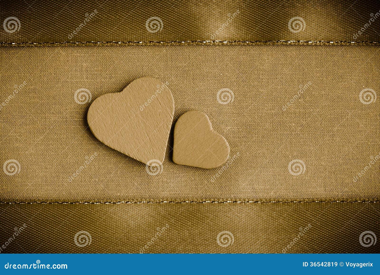 Valentinträdekorativa hjärtor på guld- torkdukebakgrund