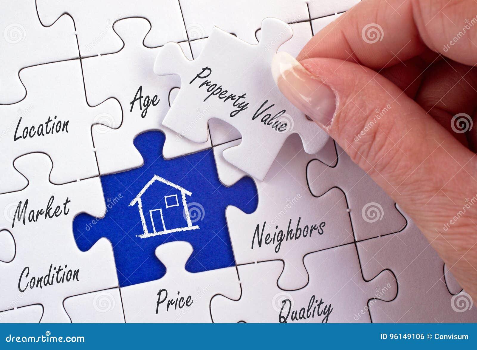 Valeur d une propriété - main femelle avec le puzzle d immobiliers