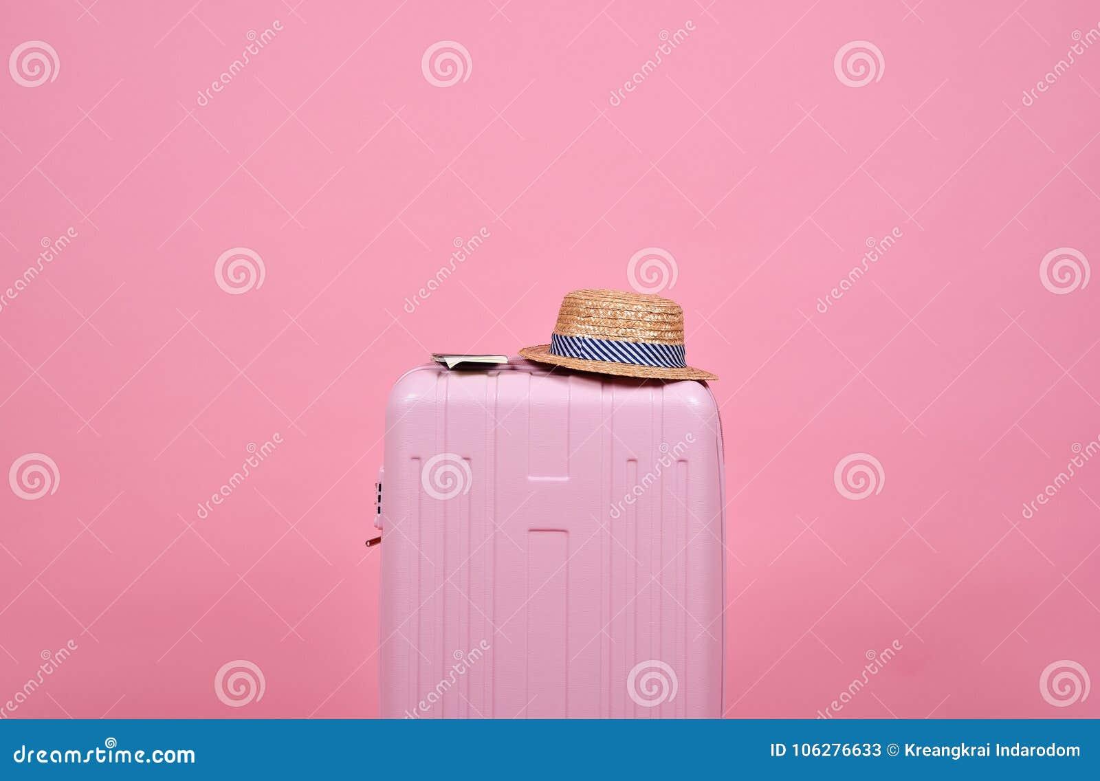 Valigia del viaggiatore e documento rosa del passaporto sopra fondo, il viaggio ed il viaggio rosa