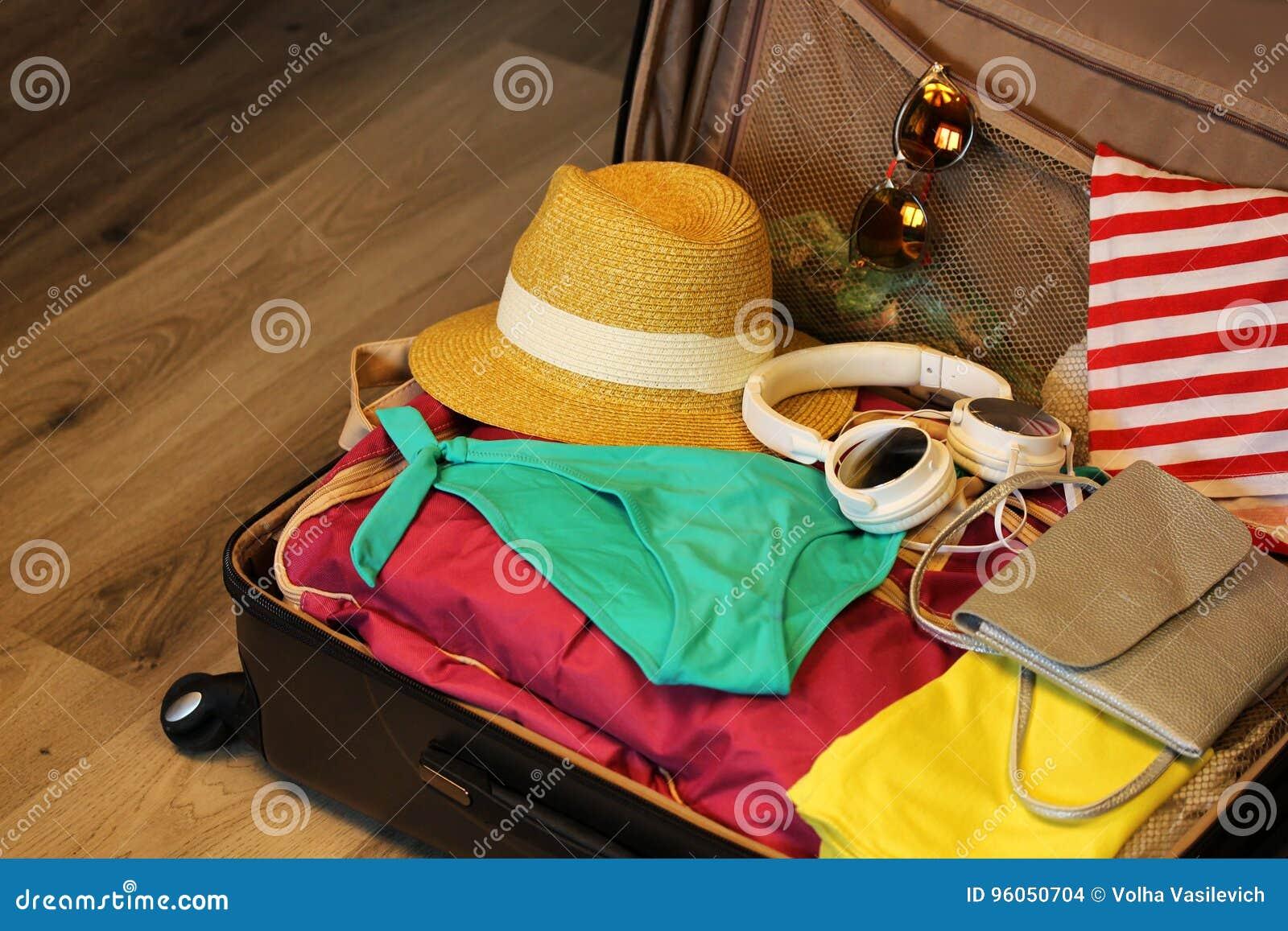 Valise rassemblée pour le voyage Valise en plan rapproché ouvert de vue avec des choses au repos sur un fond en bois