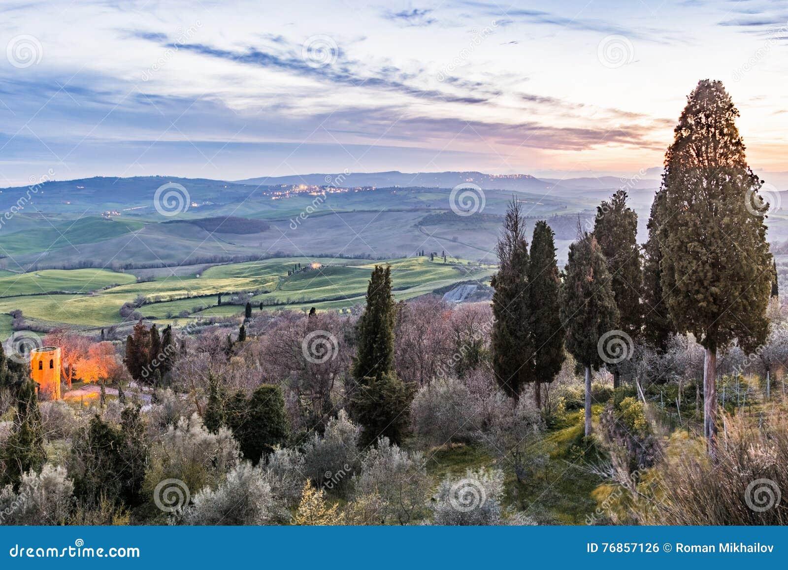 Vallée accidentée toscane avec des arbres de couleur après coucher du soleil