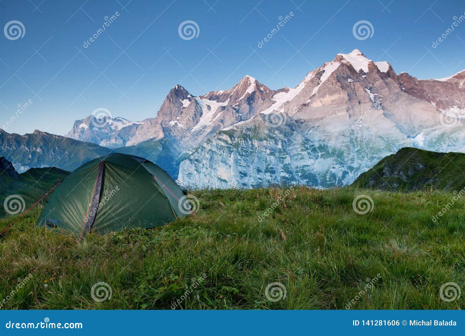 Vallée alpine rougeoyant par lumière du soleil Tente verte dans le pâturage Attraction touristique populaire Scène dramatique et