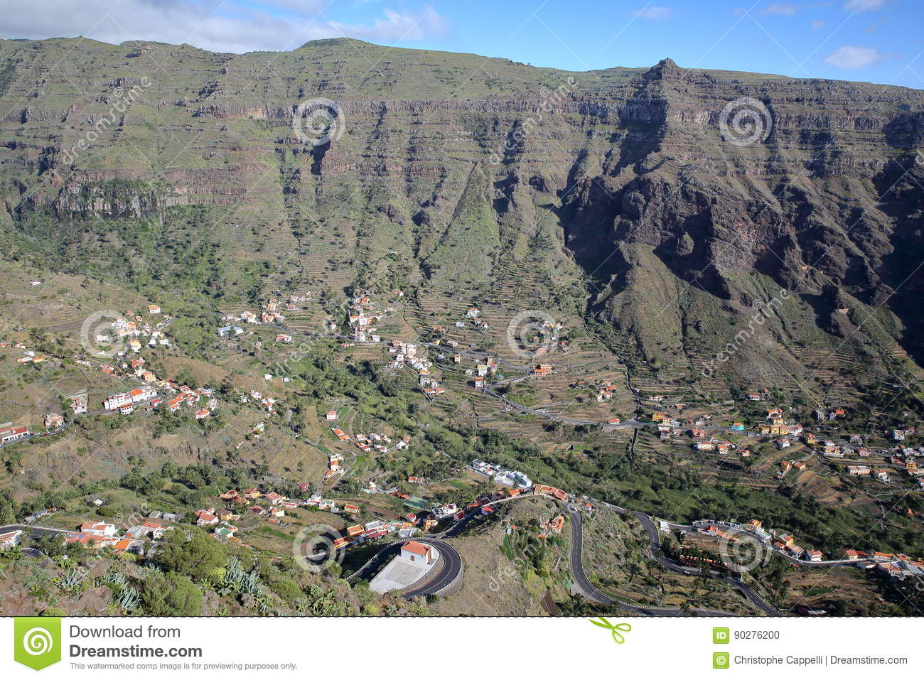 VALLE GRAN REY, LA GOMERA, SPAIN: General view of the valley with terraced fields and mountains. Winding road in the foreground