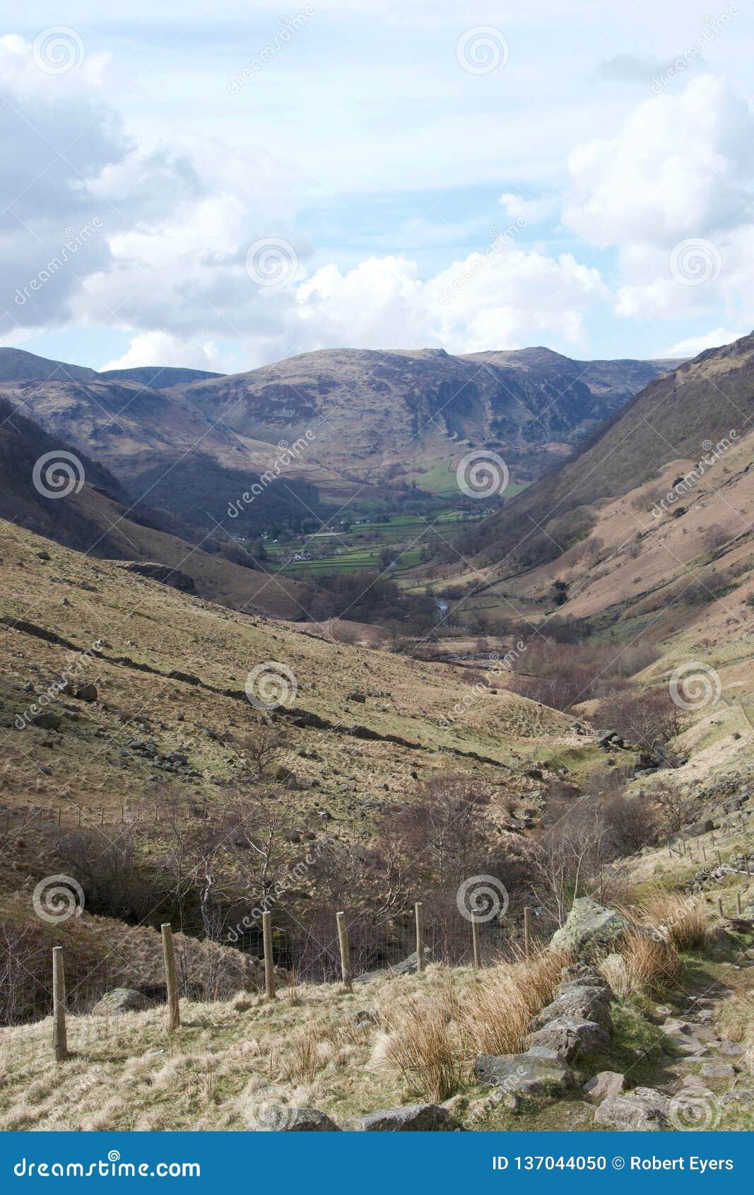 Vallei in Meerdistrict Cumbria, het UK; groene landbouwgrond in afstand en omheining in voorgrond